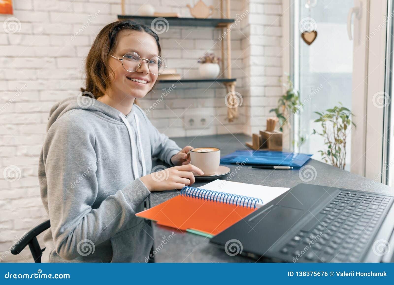Il ritratto di giovane studentessa, dello studente della High School in caffetteria con il computer portatile e della tazza di ca