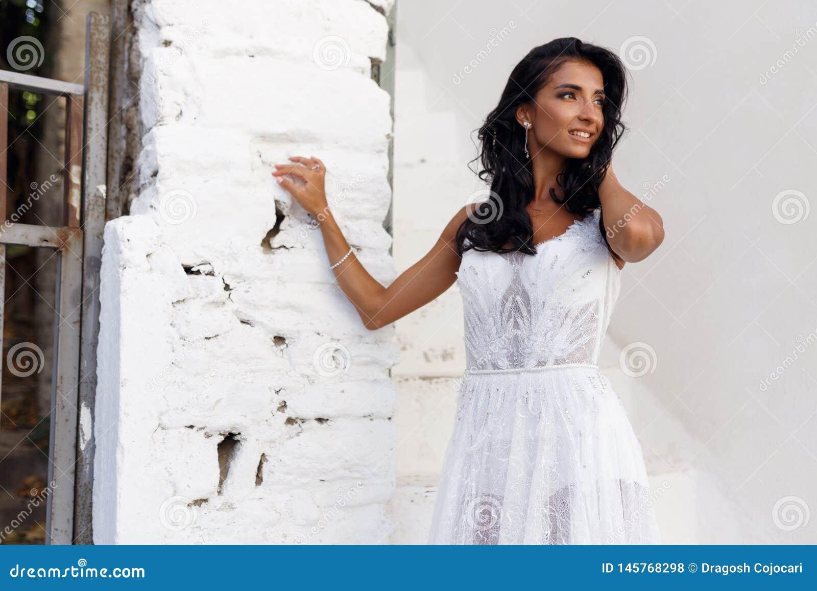 Il ritratto di profilo di una sposa in un vestito da sposa bianco, toccante leggermente i suoi capelli, posa vicino ad una parete