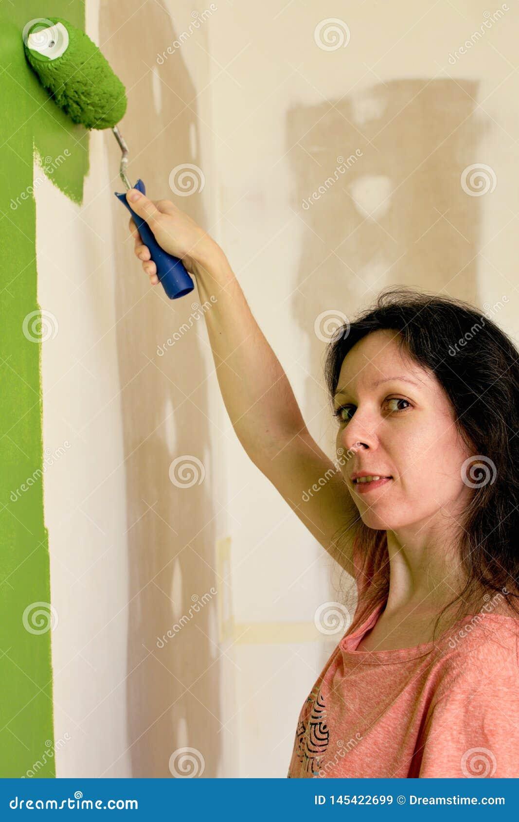 Il ritratto di una giovane donna graziosa in maglietta rosa sta dipingendo la parete interna verde con il rullo in una nuova casa