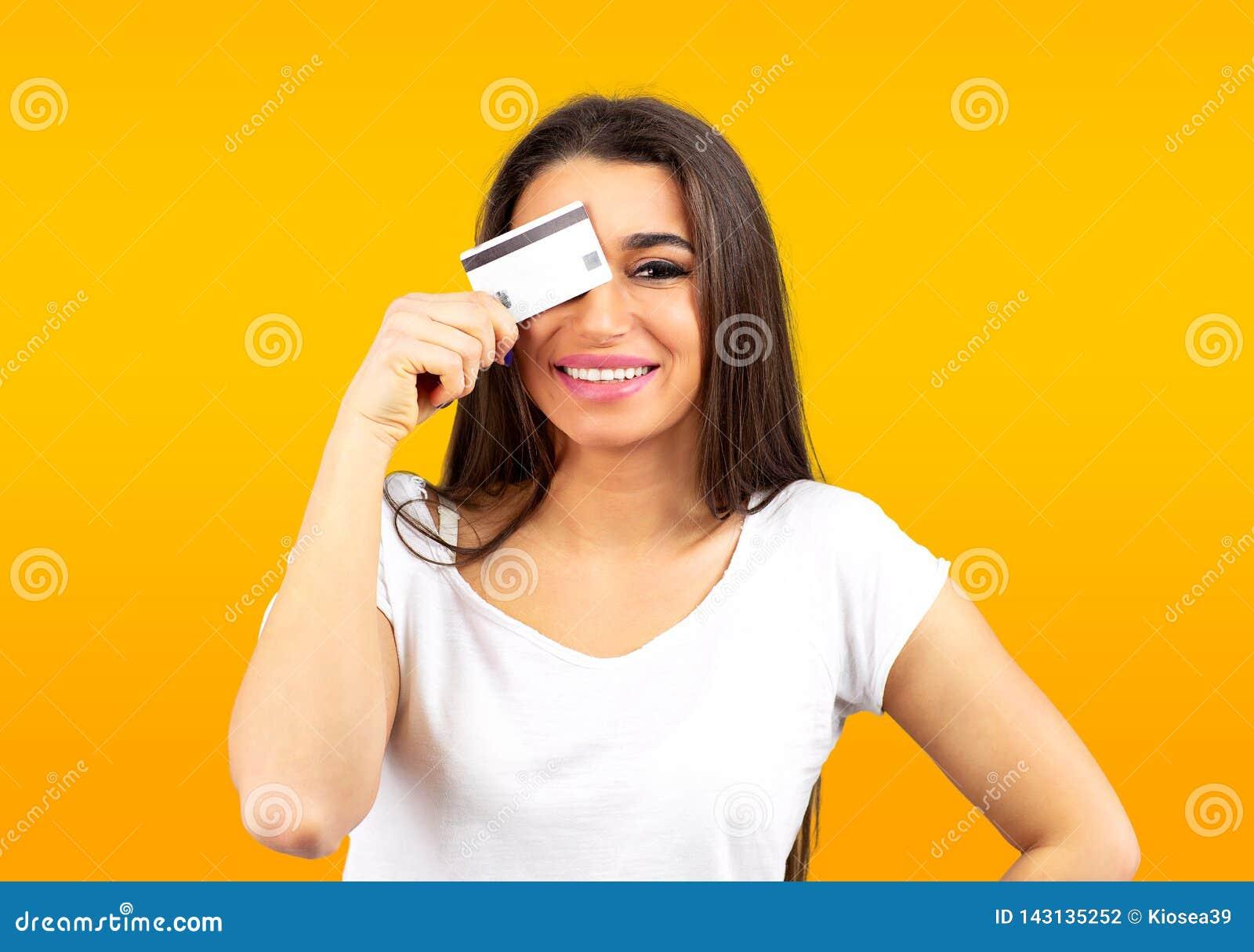 Il ritratto di una giovane donna sveglia ha vestito con indifferenza la tenuta della carta di credito al suo fronte