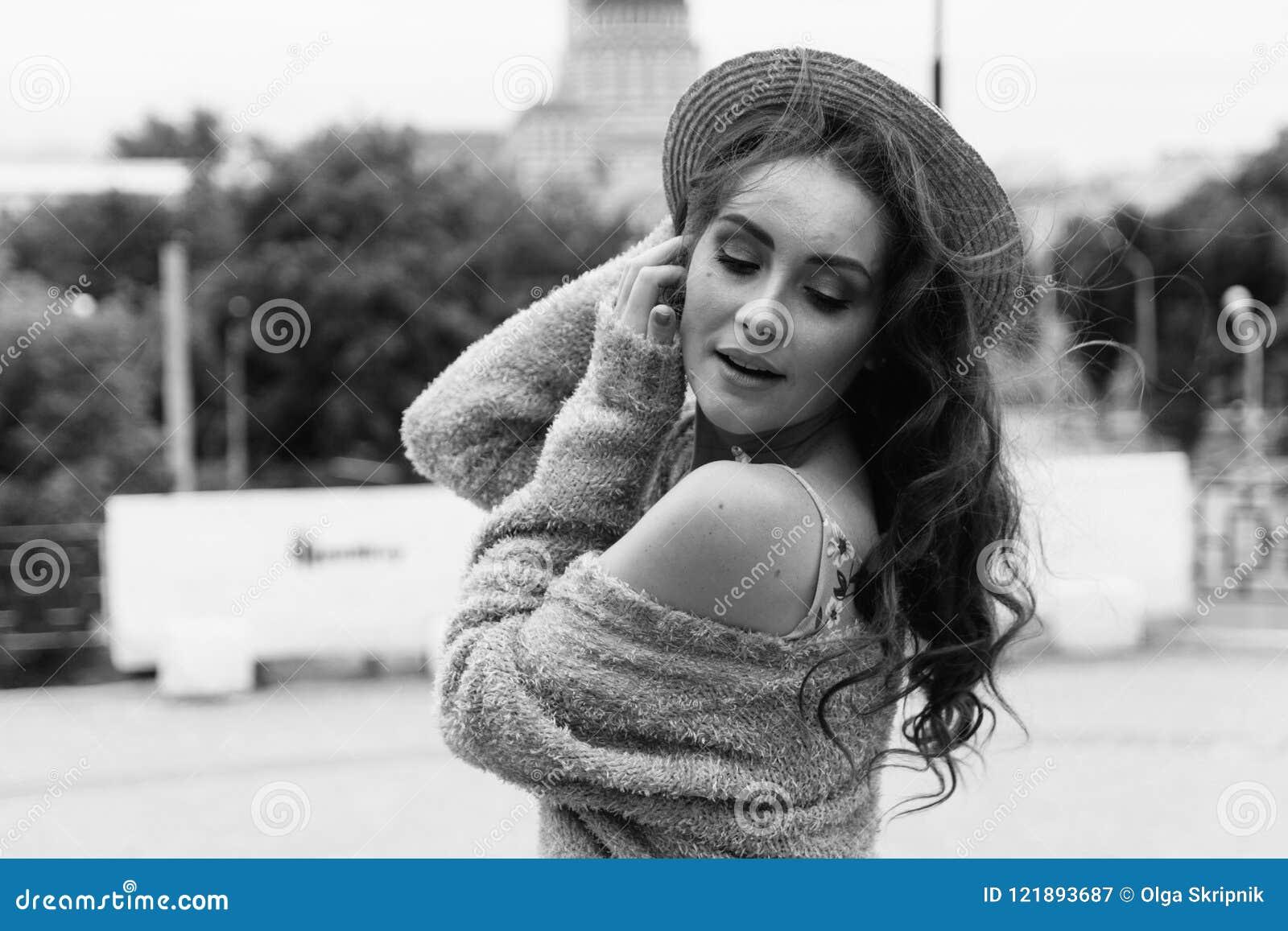 Il ritratto una bella ragazza in un cappello, si siede sui residui tiene i capelli dal vento Passeggiata intorno alla città ritra