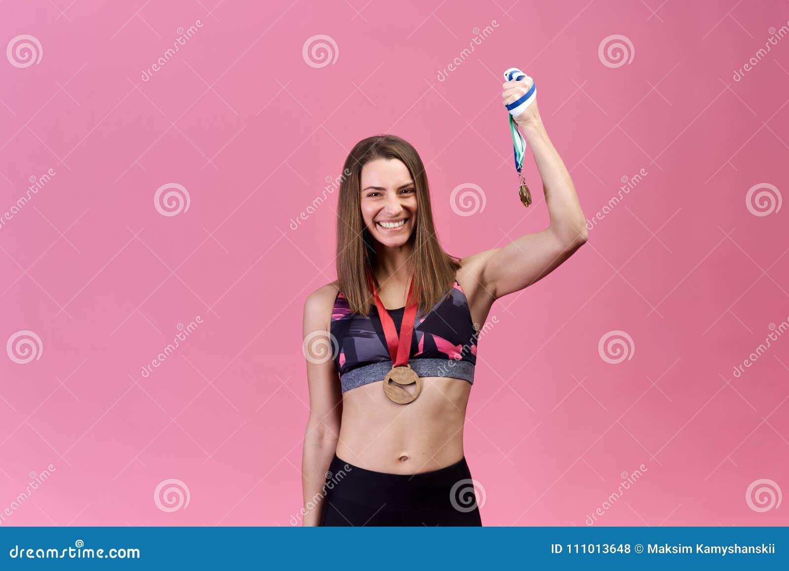 Il riuscito bello atleta della ragazza su fondo isolato mostra la vittoria, il successo, medaglie