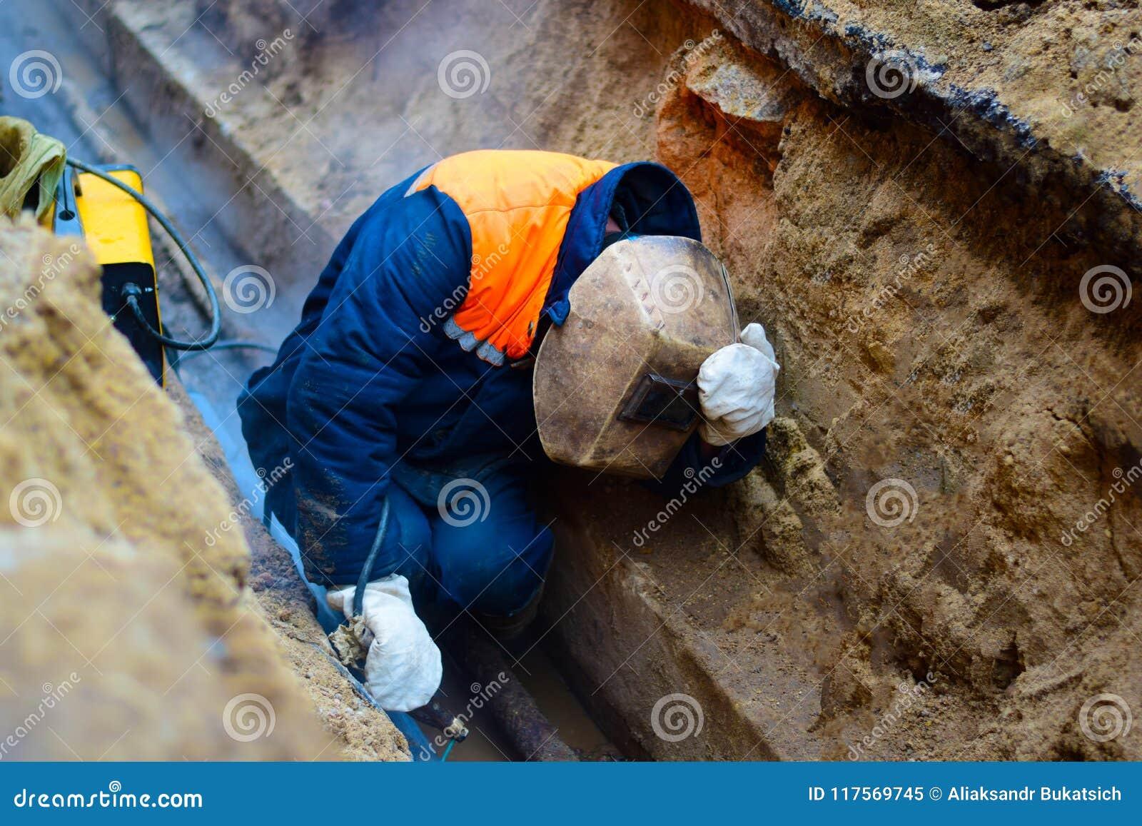 Il saldatore ripara la conduttura nella miniera