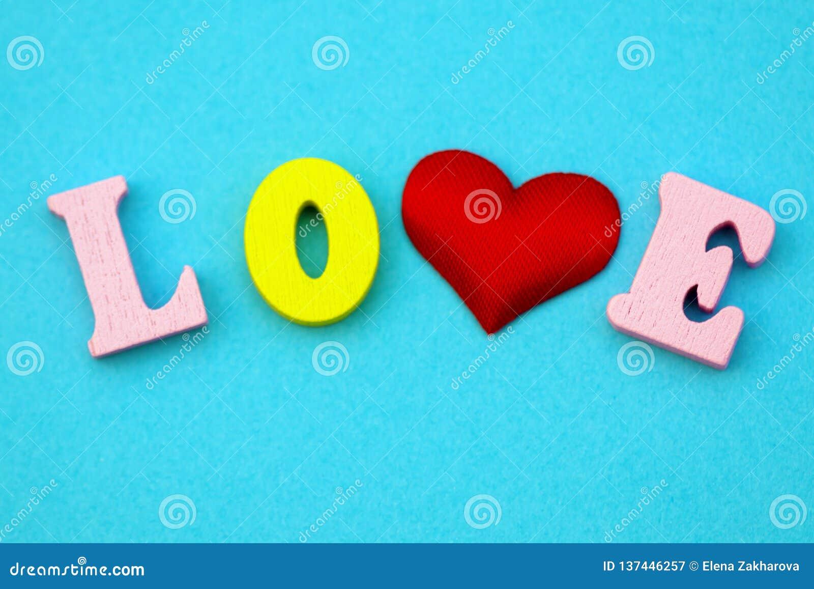 Il San Valentino di amore di parola con le lettere di legno variopinte Amore e cuore - un simbolo del San Valentino Macro