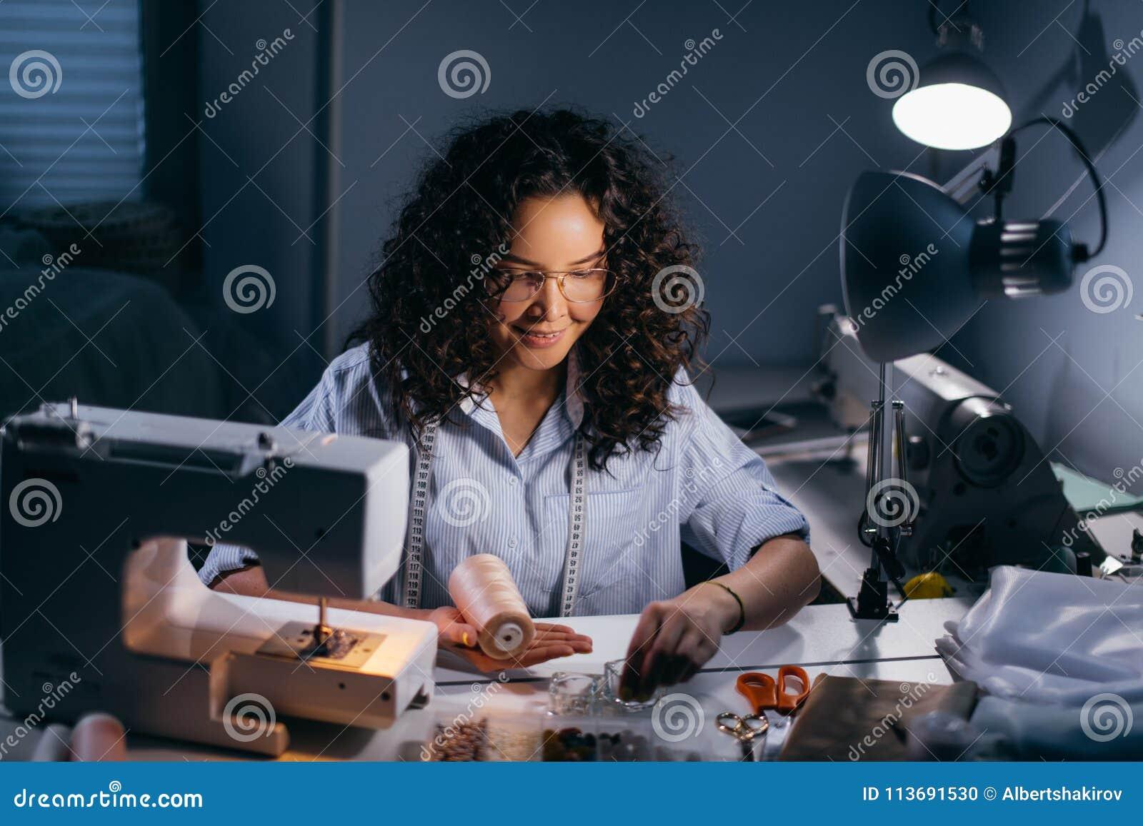 Il sarto da donna sta infilando le perle davanti alla macchina di cucitura nella stanza nera