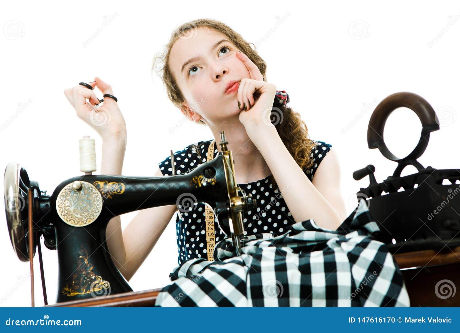 Il sarto da donna Teenaged della ragazza ritiene ed il piano prima userà la macchina per cucire manuale