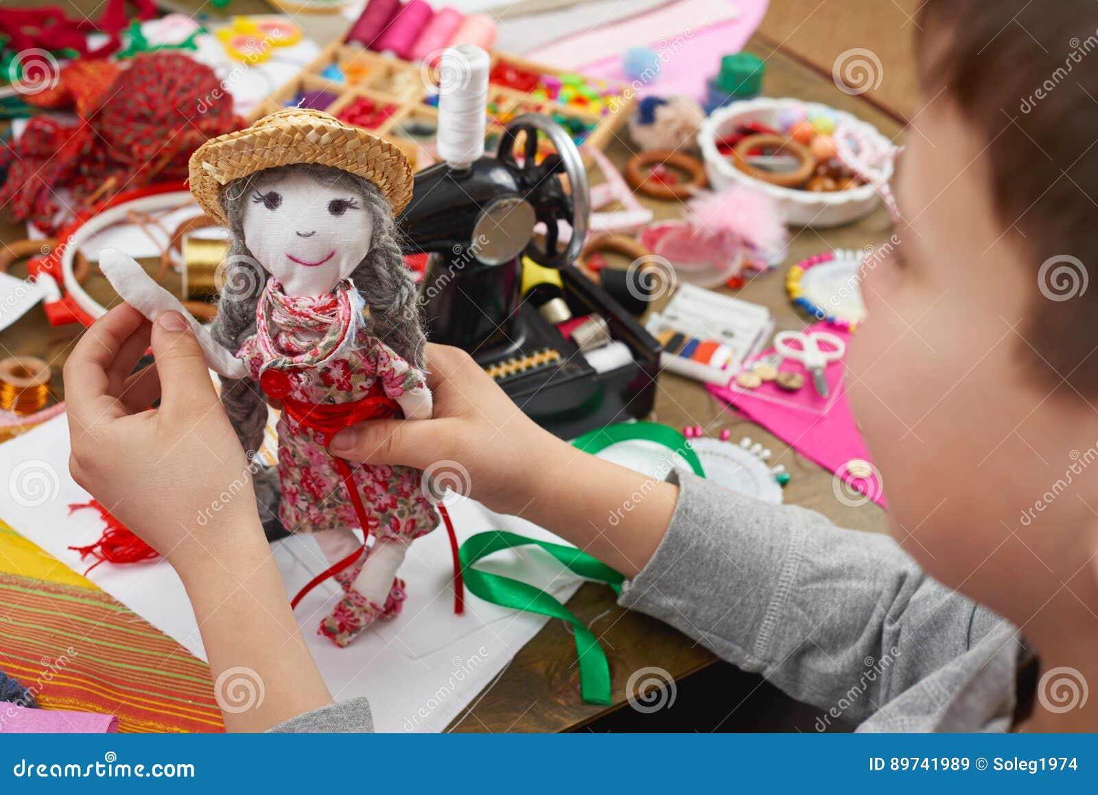 Il sarto del ragazzo impara cucire, vestirsi per il concetto fatto a mano e dell artigianato della bambola,