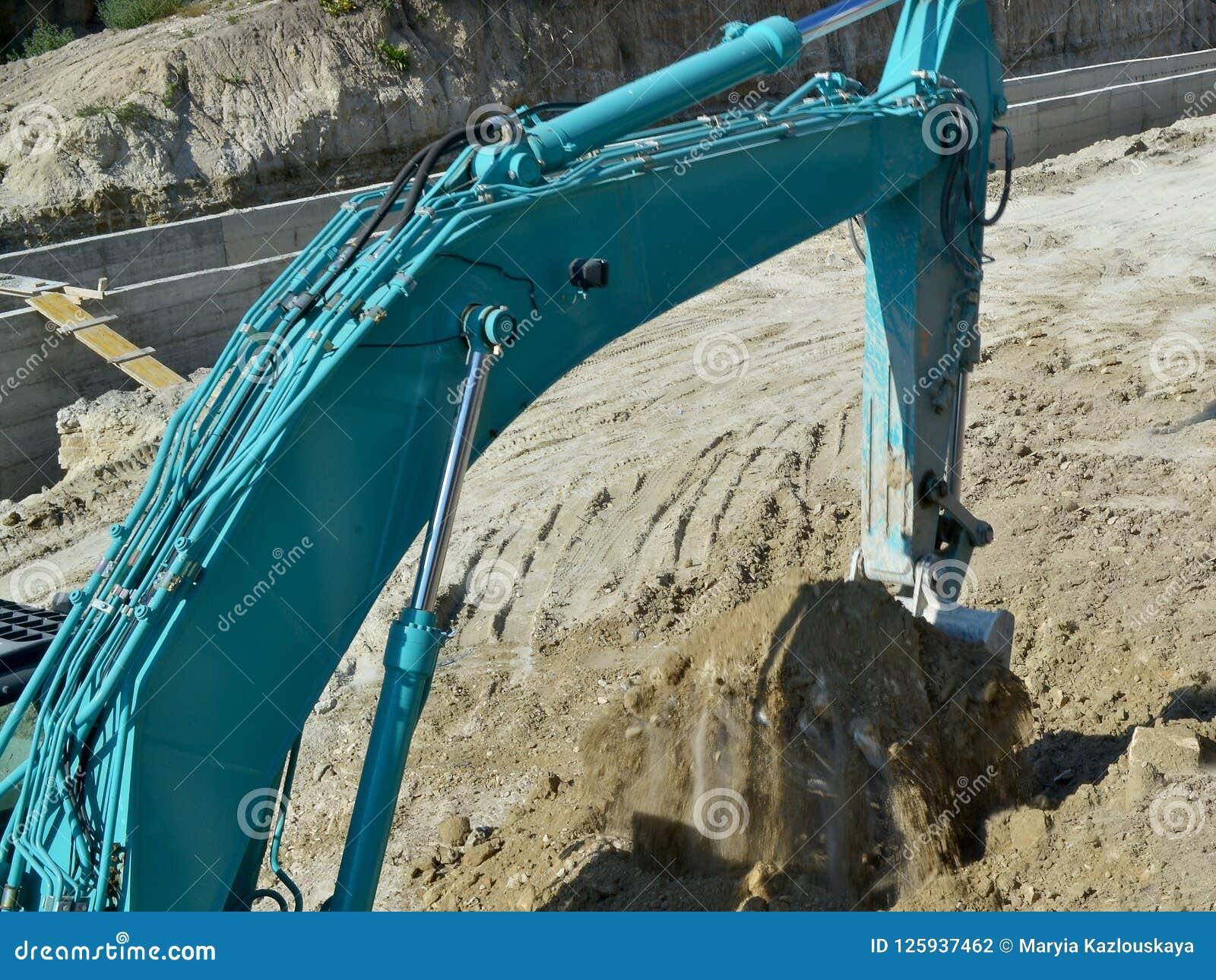 Il secchio di un escavatore blu ha scavato appena sulla terra al sito dei lavori stradali