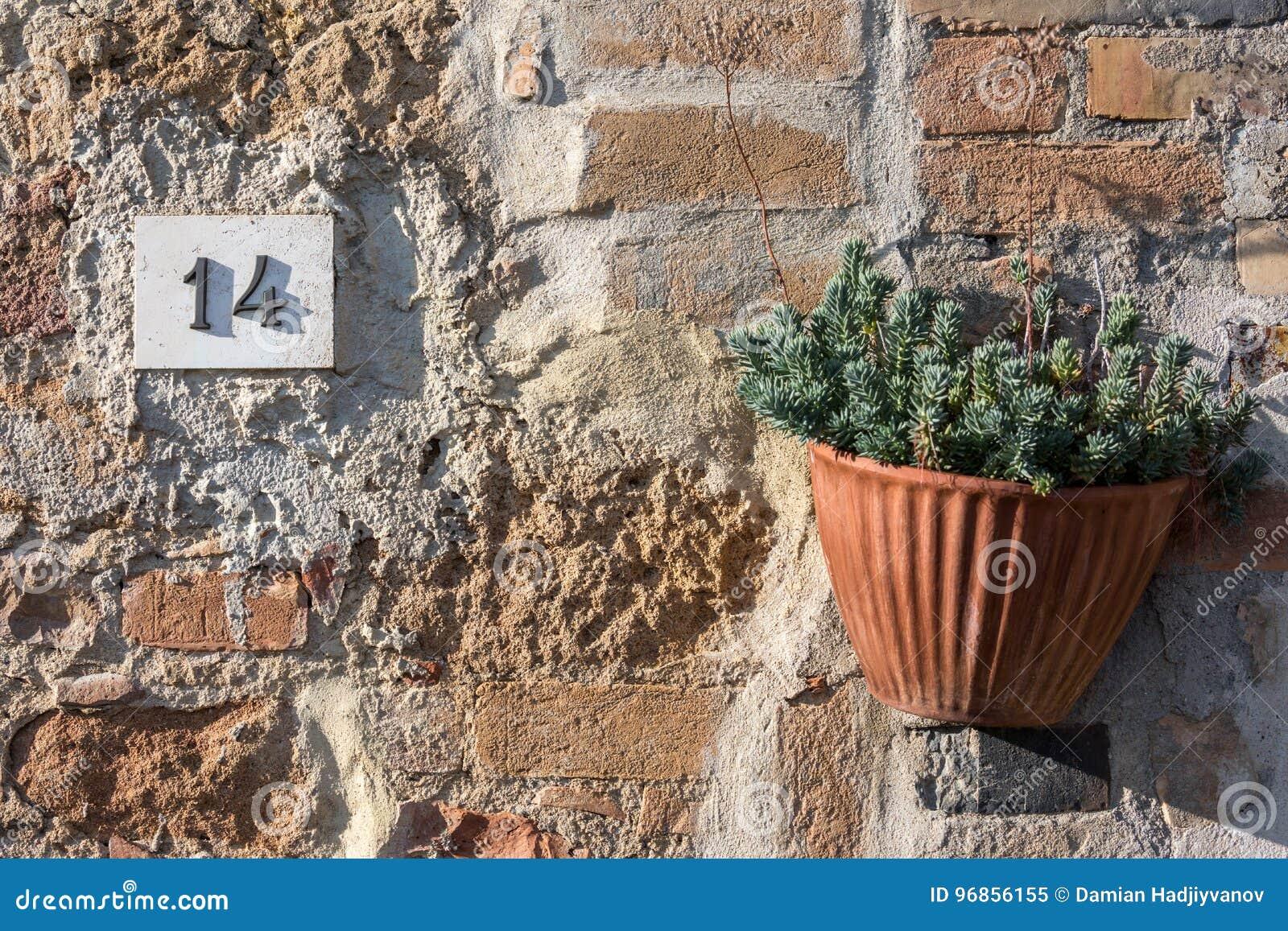 Il segnale stradale su una casa che legge il numero quattordici ha fatto dalle cifre metalliche su una base di marmo