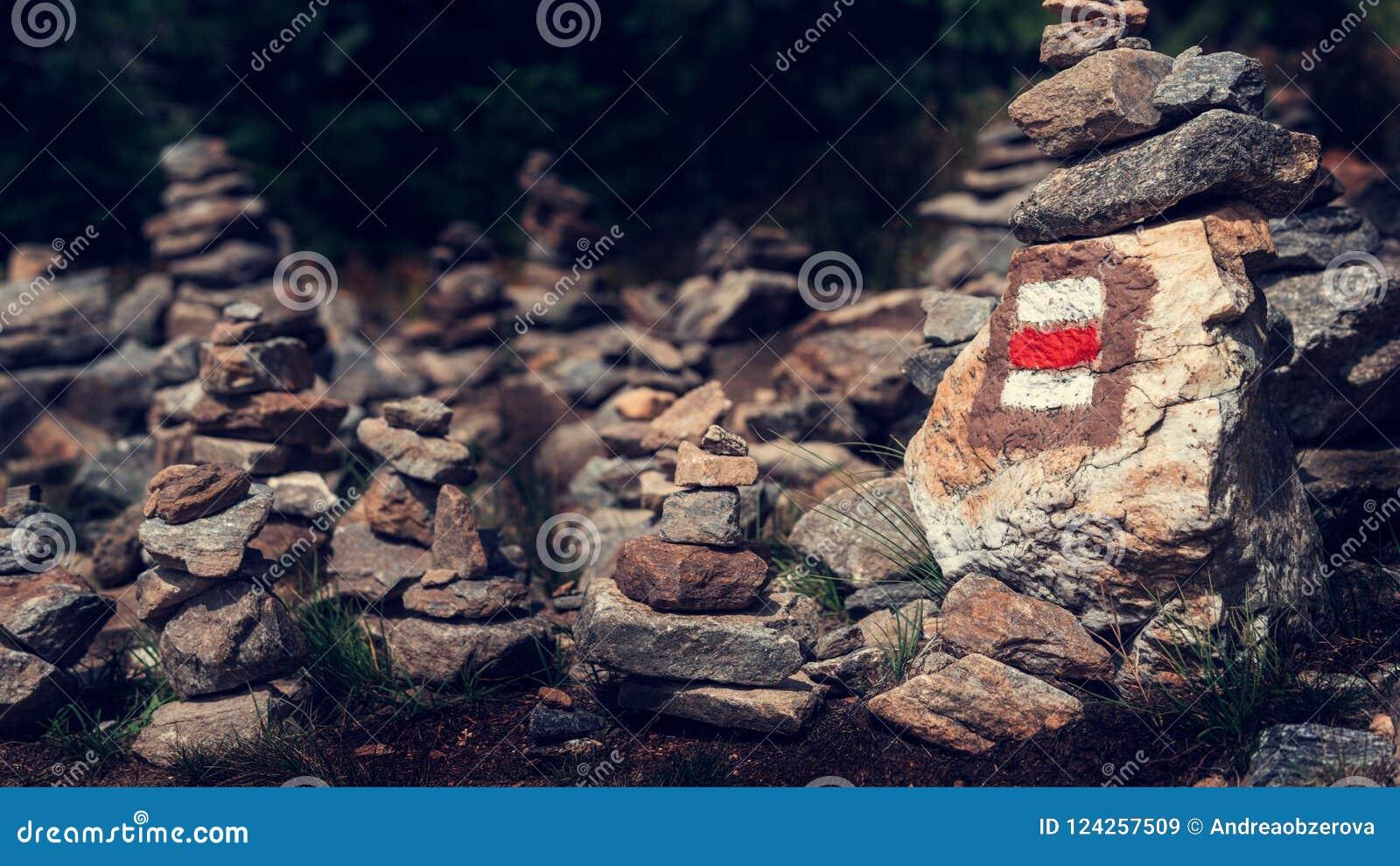 Il segno della traccia di escursione segna dipinto su una roccia in pila di pietre di zen Depressione principale del percorso bel