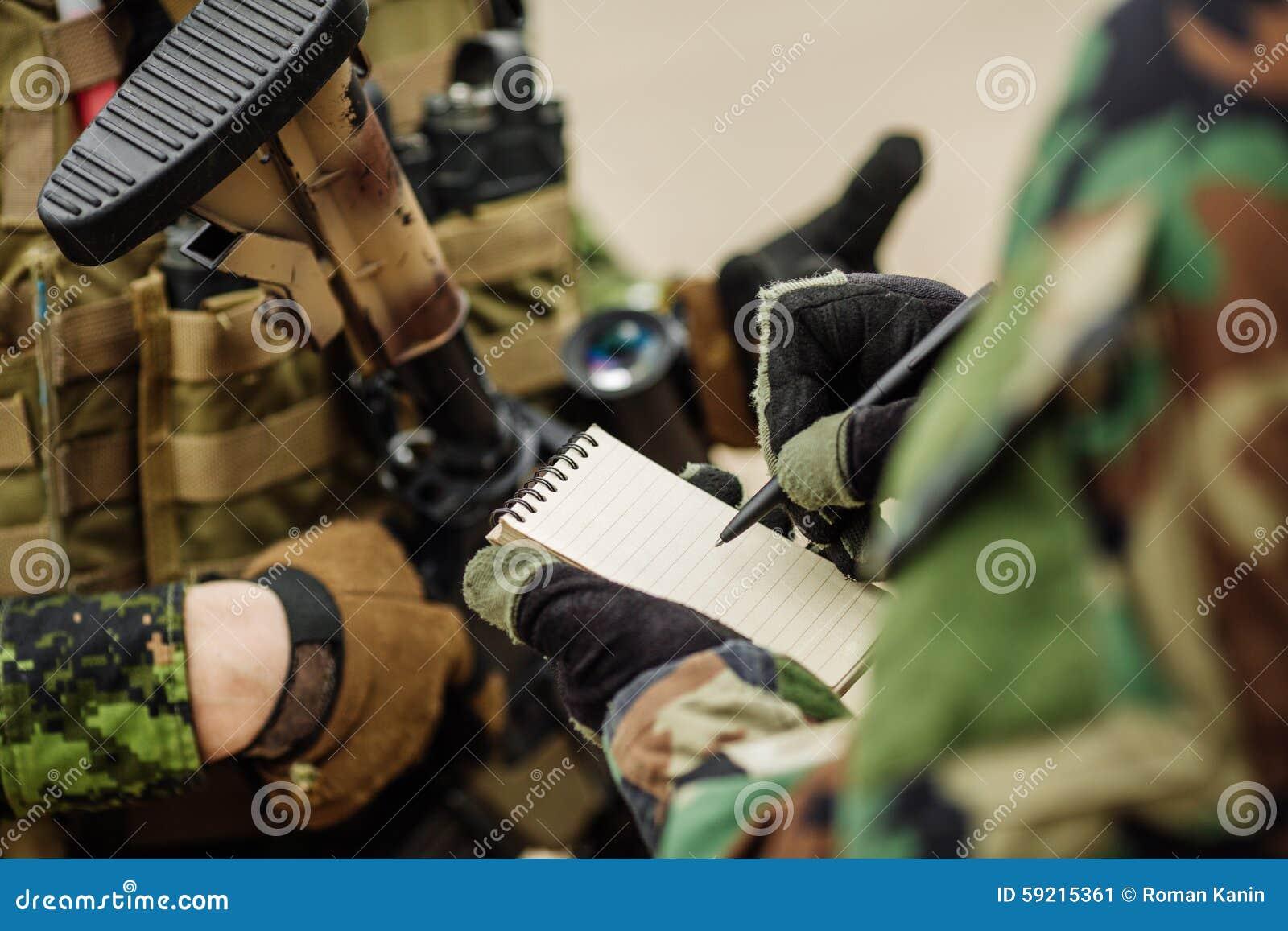 Il soldato ha scritto la penna in un piano d azione del taccuino