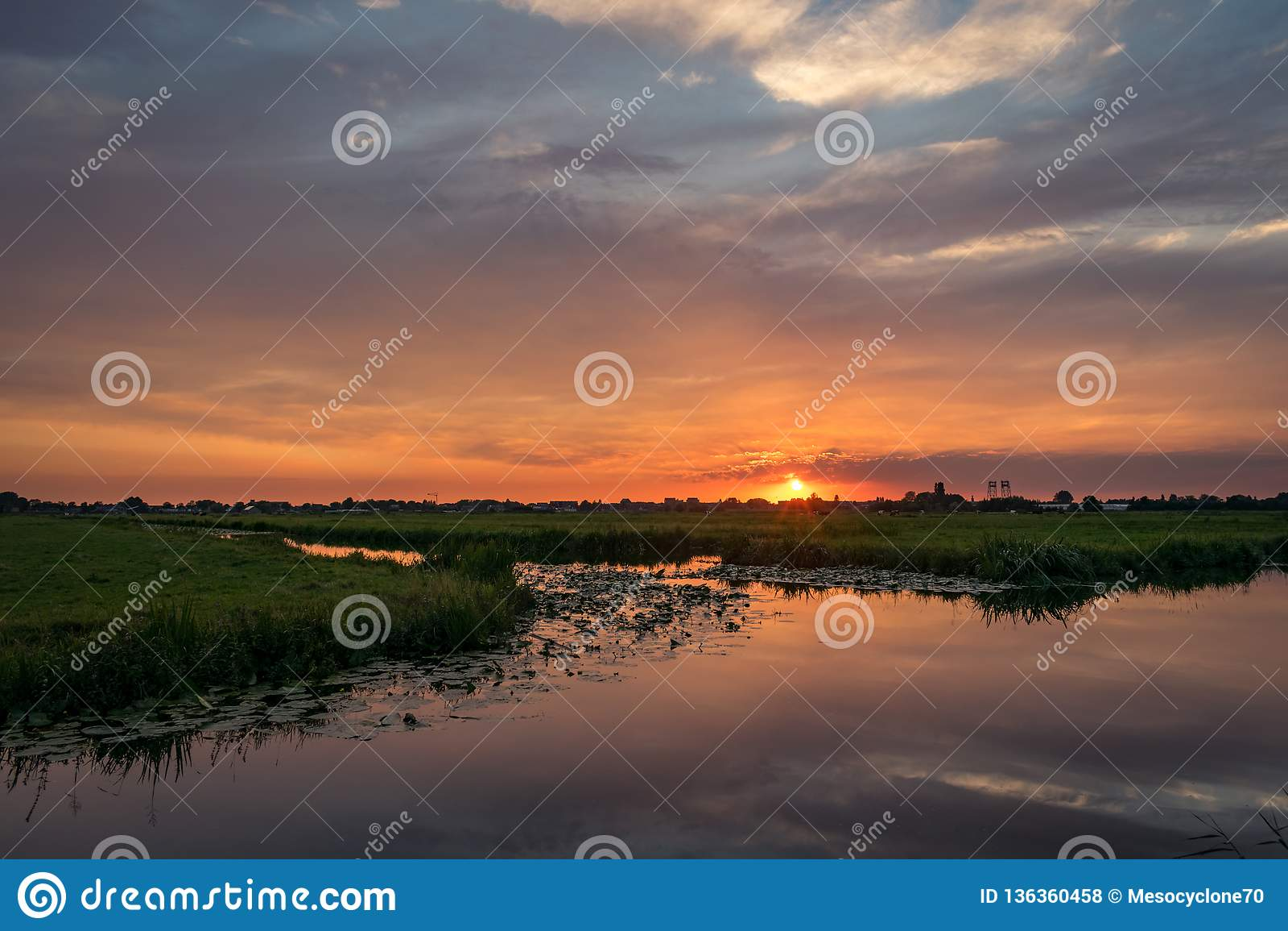 Il sole mette sull orizzonte della campagna olandese Un bello cielo colorato è riflesso nell acqua di un lago