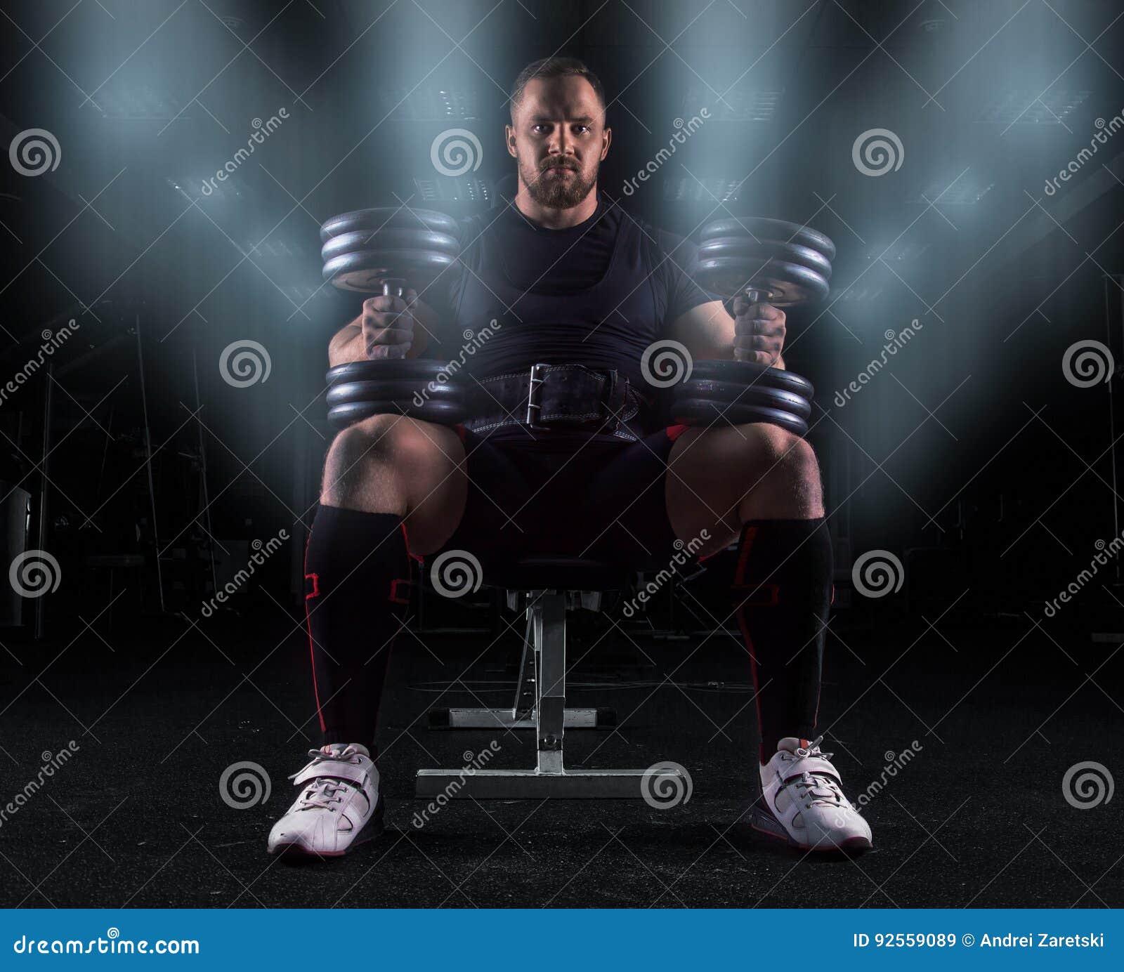 Il sollevatore pesi professionale si siede su un banco con due teste di legno sopra