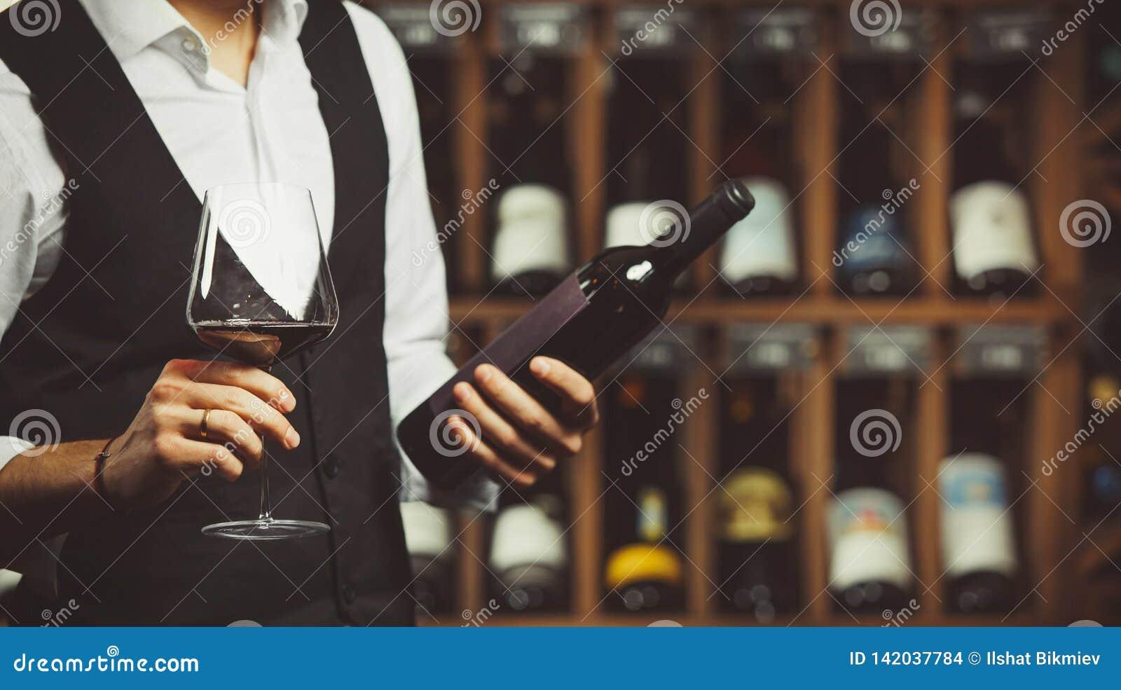 Il sommelier assaggia il vino rosso e legge l etichetta della bottiglia, primo piano sparato sul fondo della cantina