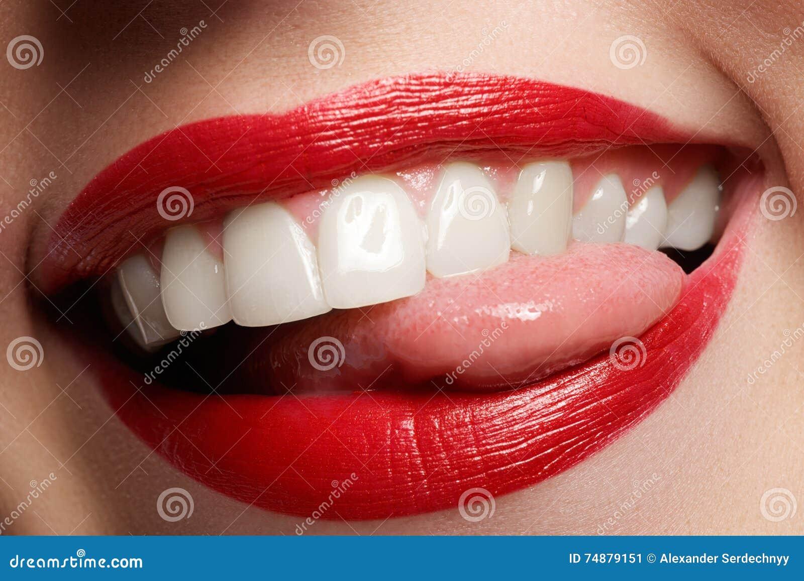Il sorriso femminile felice del primo piano con i denti bianchi sani, labbra rosse luminose prepara