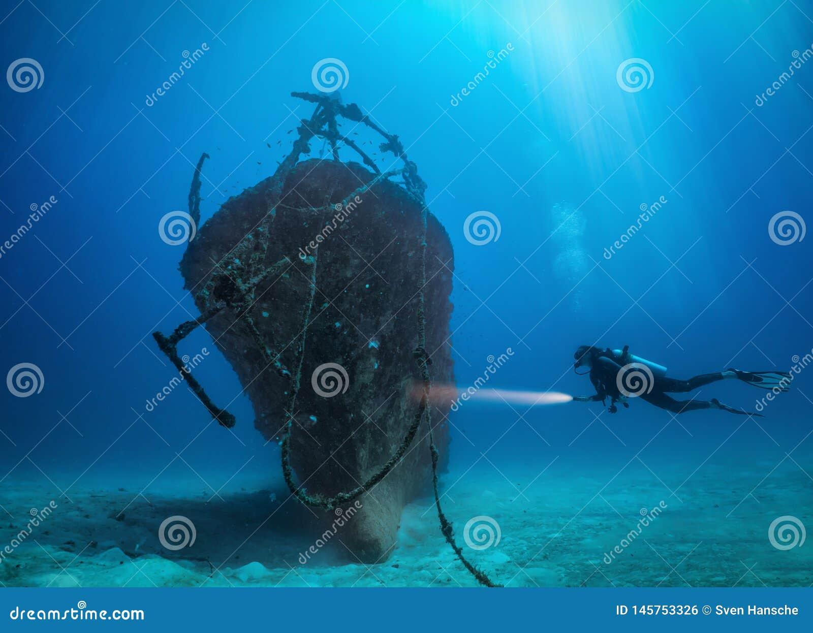 Il subaqueo femminile esplora un naufragio incavato alle isole delle Maldive