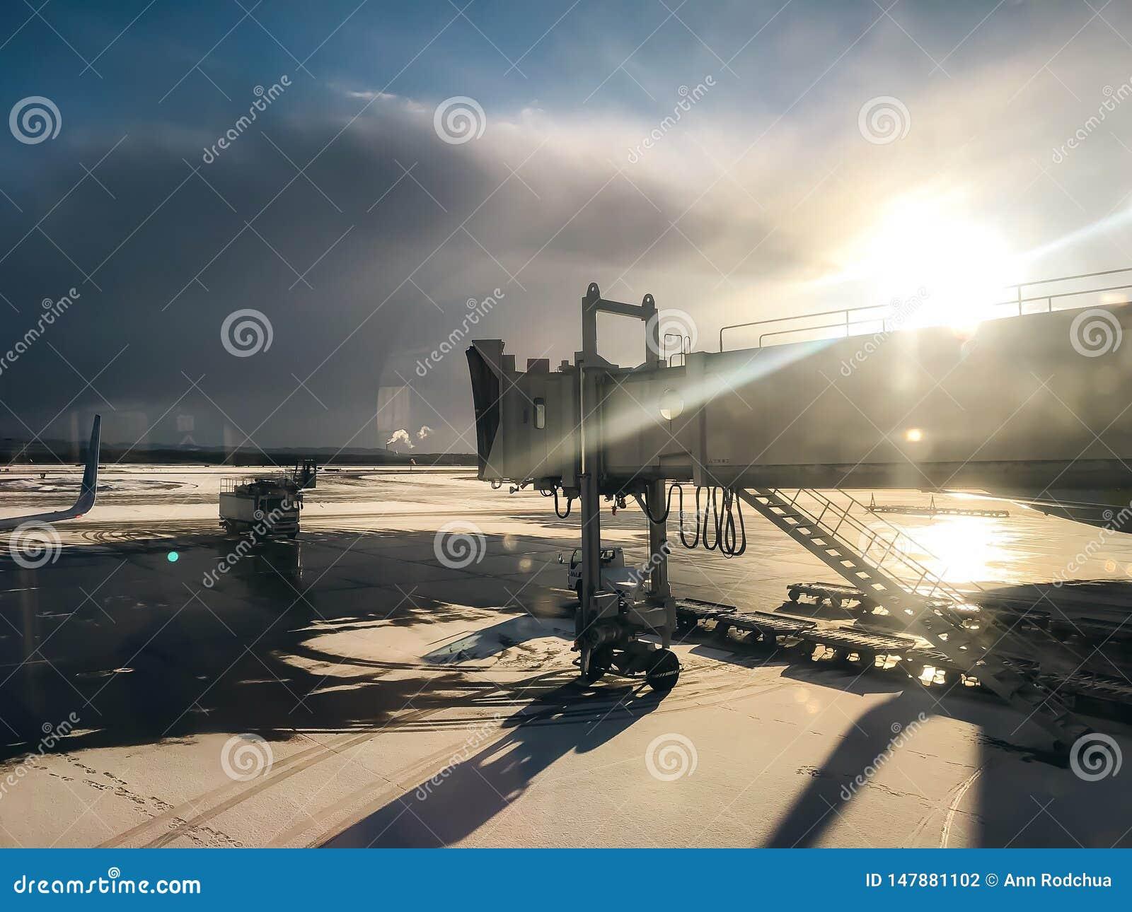 Il Sun splende dietro il ponte del getto all aeroporto