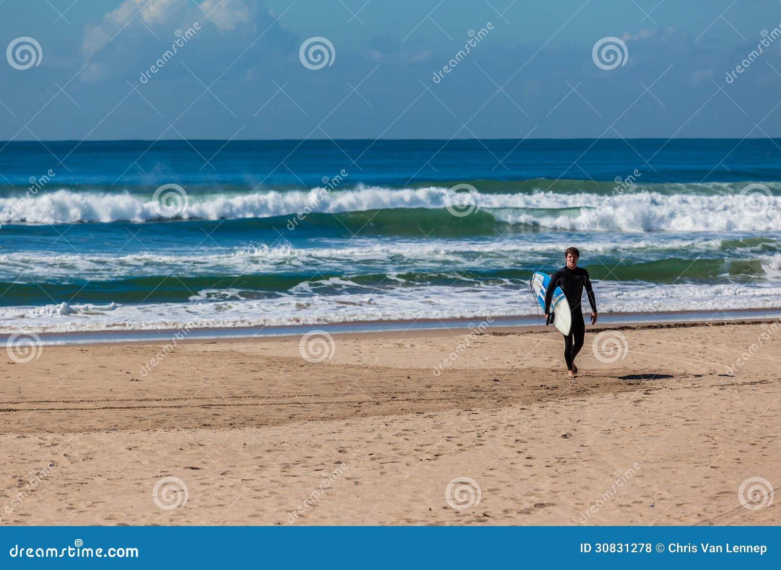Il surfista della spiaggia esce le onde