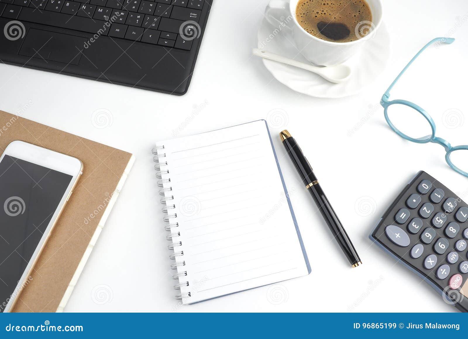Il taccuino della pagina in bianco sul desktop bianco con la penna, caffè, lapto