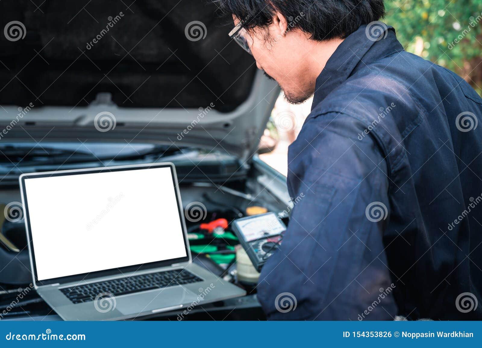 Il tecnico asiatico analizzare il grafico del motore dell automobile sul computer portatile nel garage il concetto di automobilis