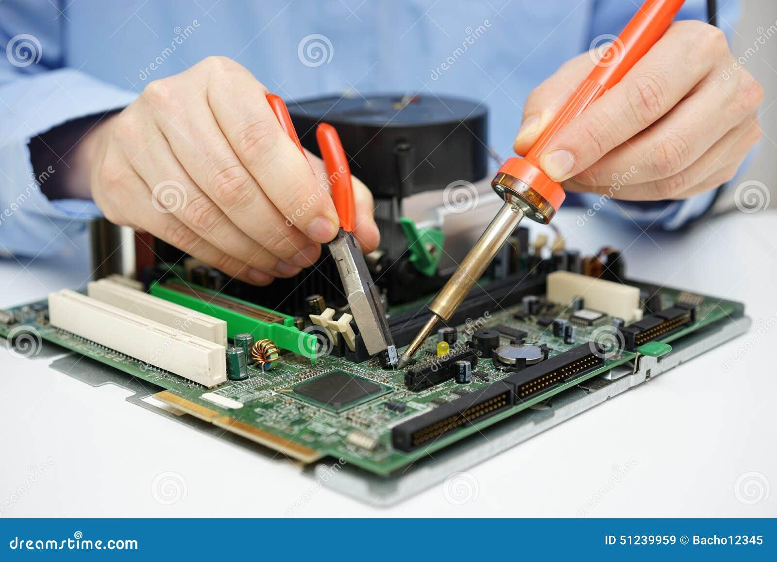 Il tecnico del computer sta cambiando il condensatore sulla scheda madre difettosa