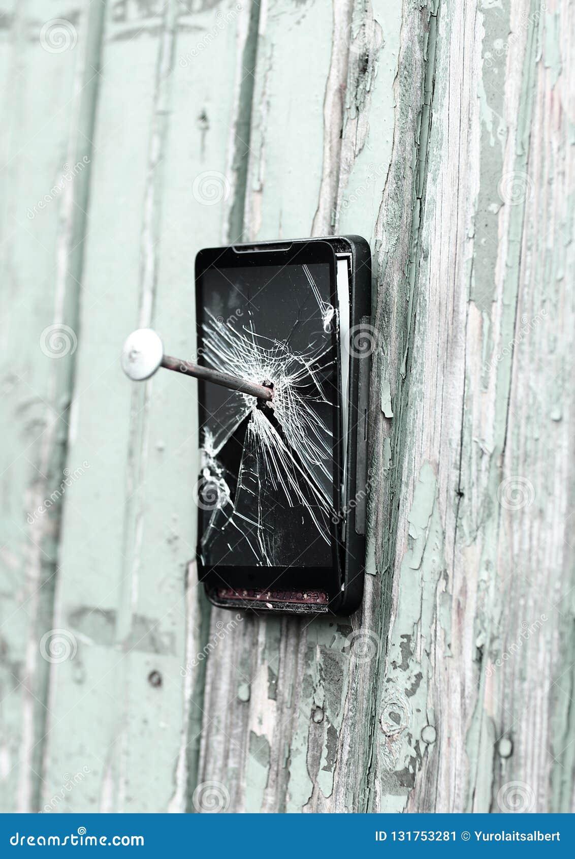 Il telefono cellulare obsoleto è inchiodato ad un recinto di legno