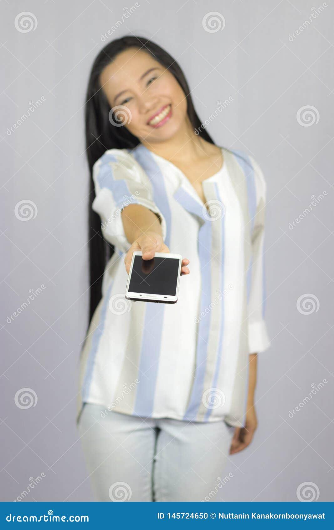 Il telefono cellulare sorridente della tenuta delle donne, d? uno Smart Phone voi Isolato su priorit? bassa grigia