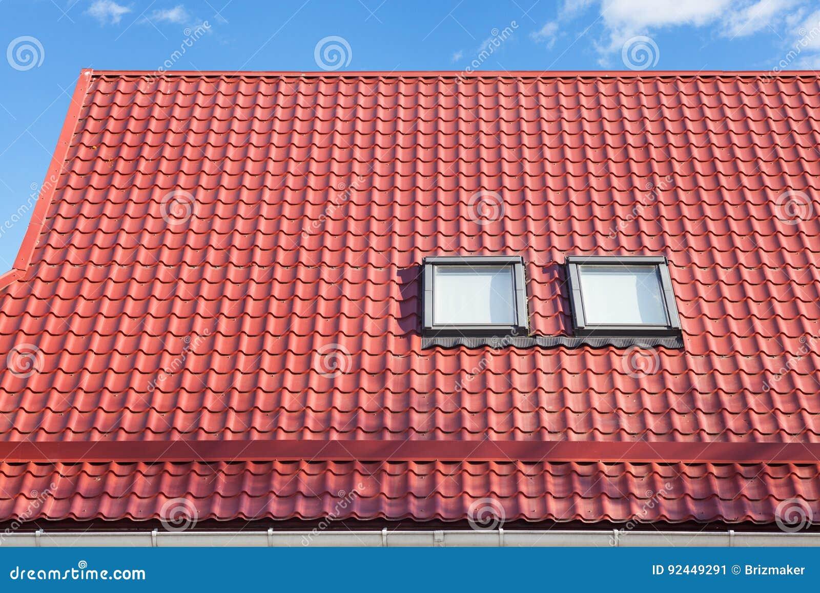Il tetto piastrellato metallo rosso con i nuovi abbaini il tetto