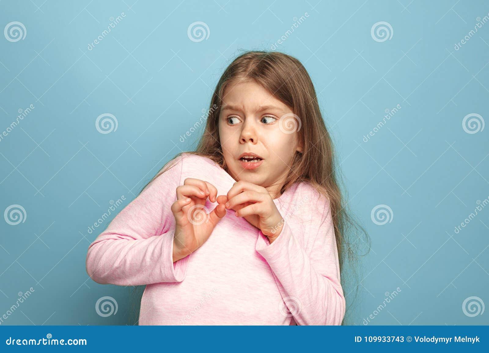 Il timore Ragazza teenager su un fondo blu Concetto di emozioni della gente e di espressioni facciali