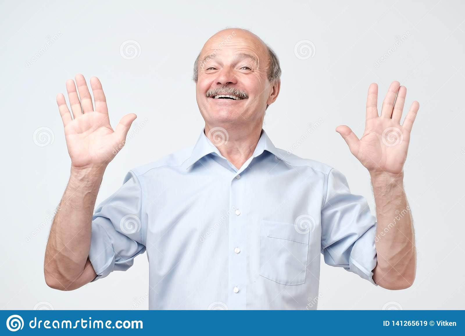 Il tipo allegro solleva le mani come le manifestazioni che sono uninvolved, ha sguardo felice