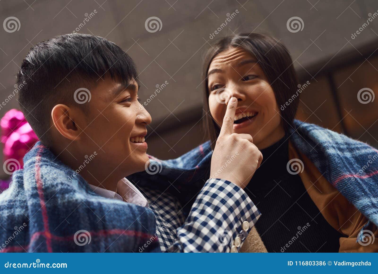 Il tipo felice tocca il naso della ragazza