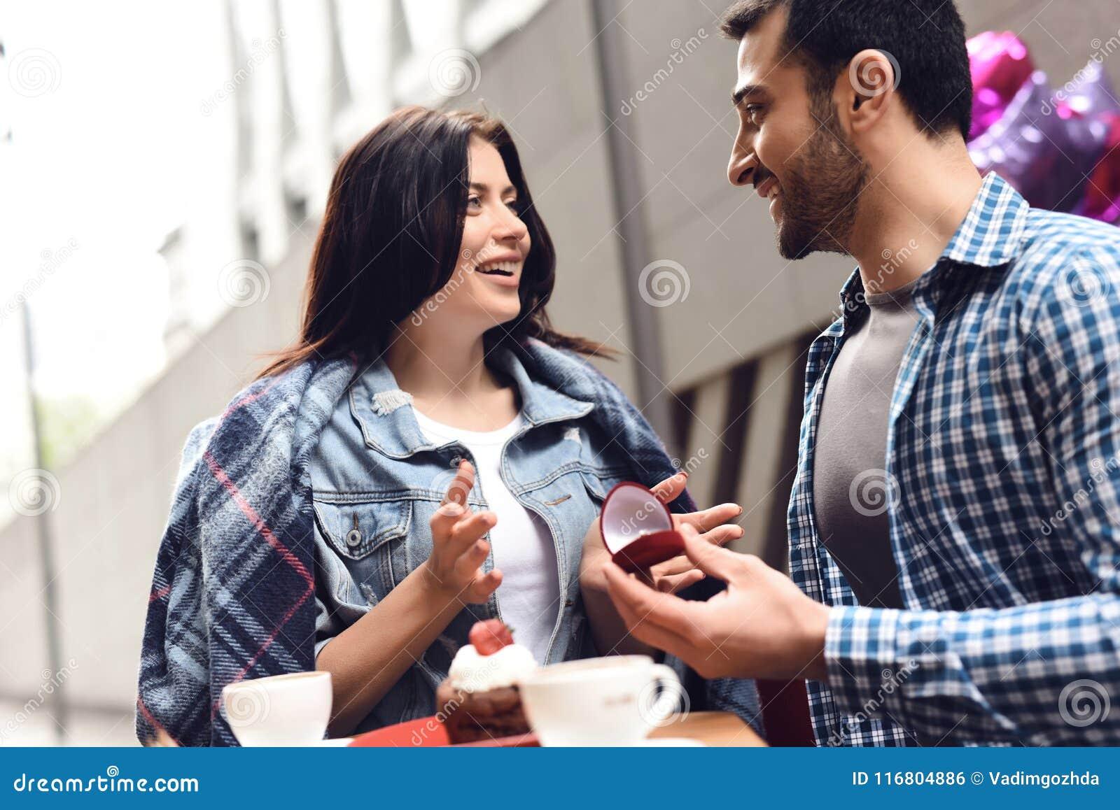 Il tipo presenta una proposta di nozze alla ragazza che si siede alla tavola in caffè