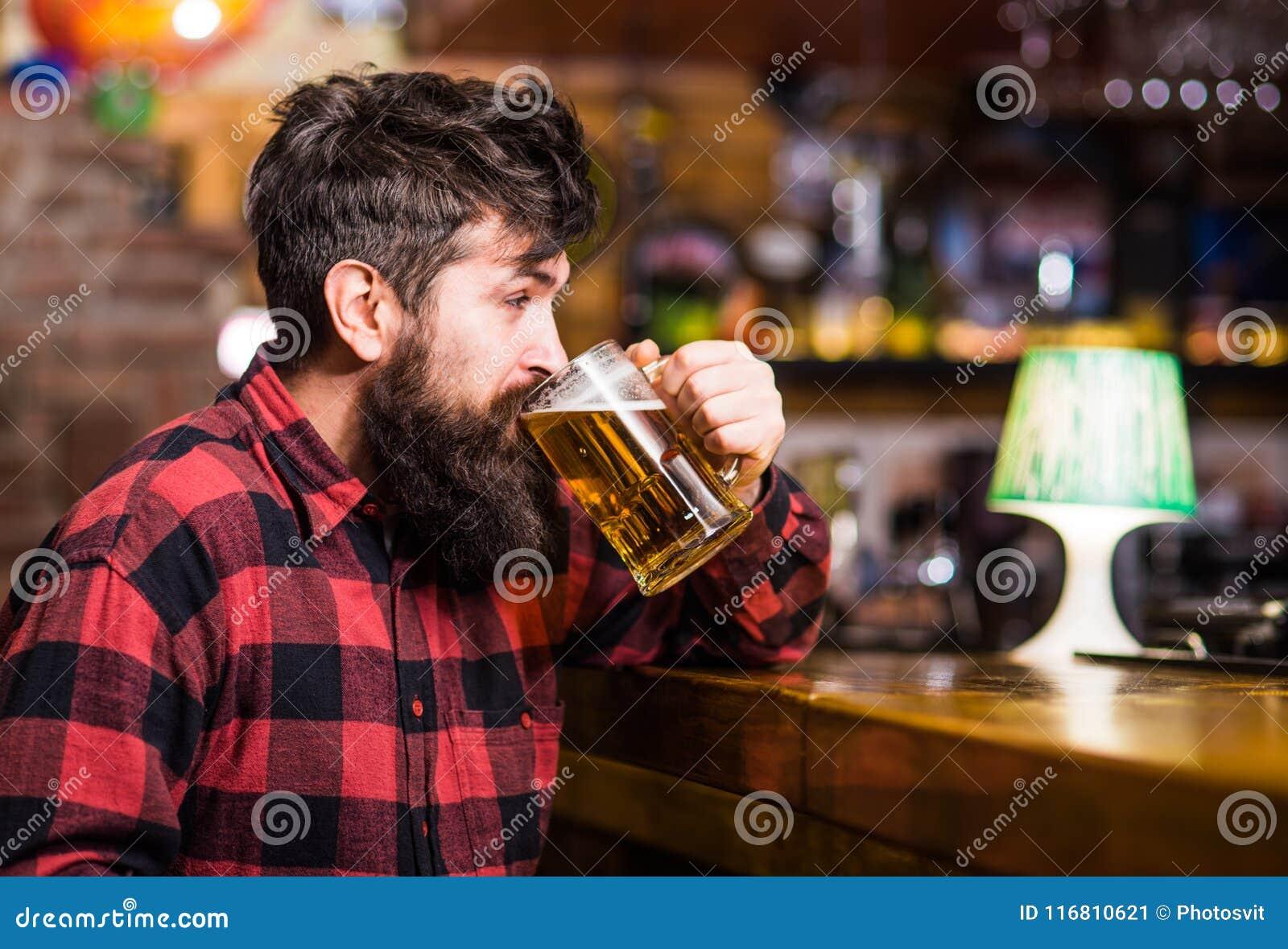 Il tipo spende lo svago nella barra, fondo defocused L uomo sul fronte calmo si siede vicino al contatore della barra, estigue i