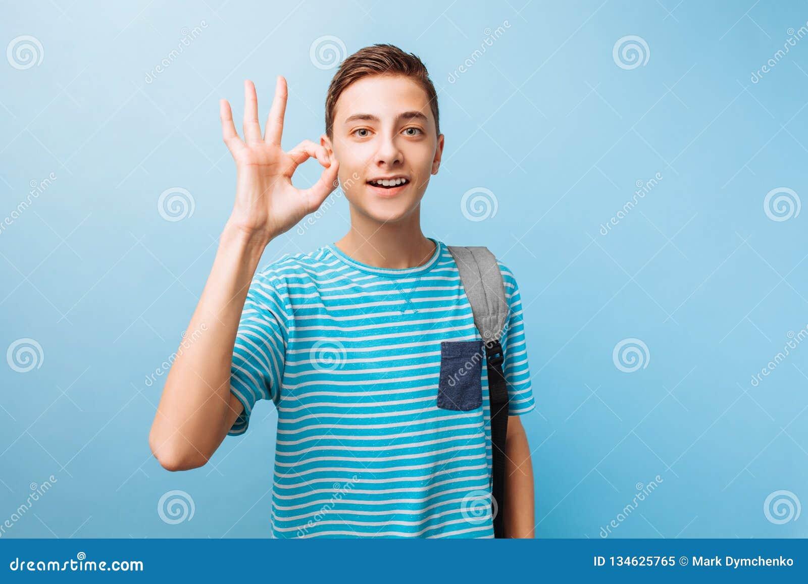 Il tipo teenager allegro esamina la macchina fotografica, mostra il segno di APPROVAZIONE