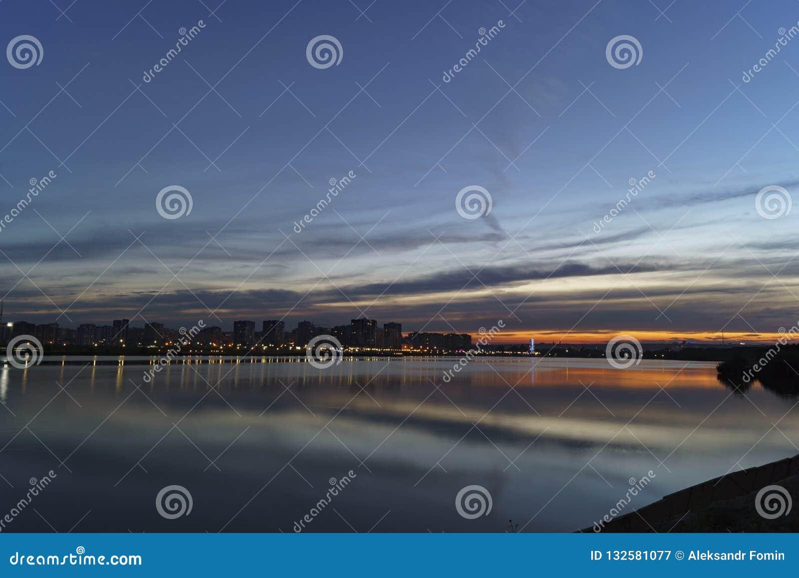 Il tramonto uguagliante sopra la città sulle banche del fiume