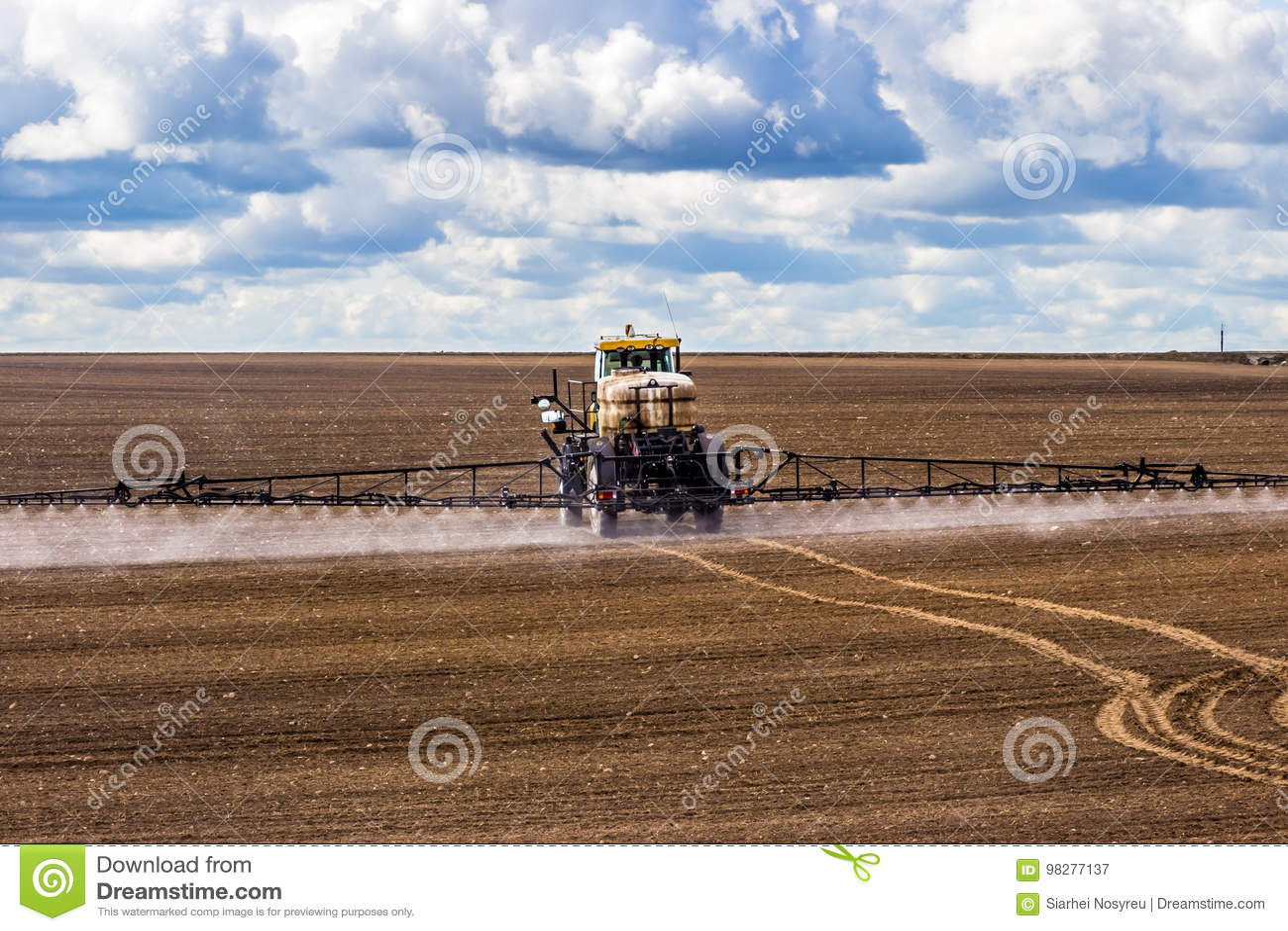Il trattore che spruzza un campo sull azienda agricola, fertilizza la terra