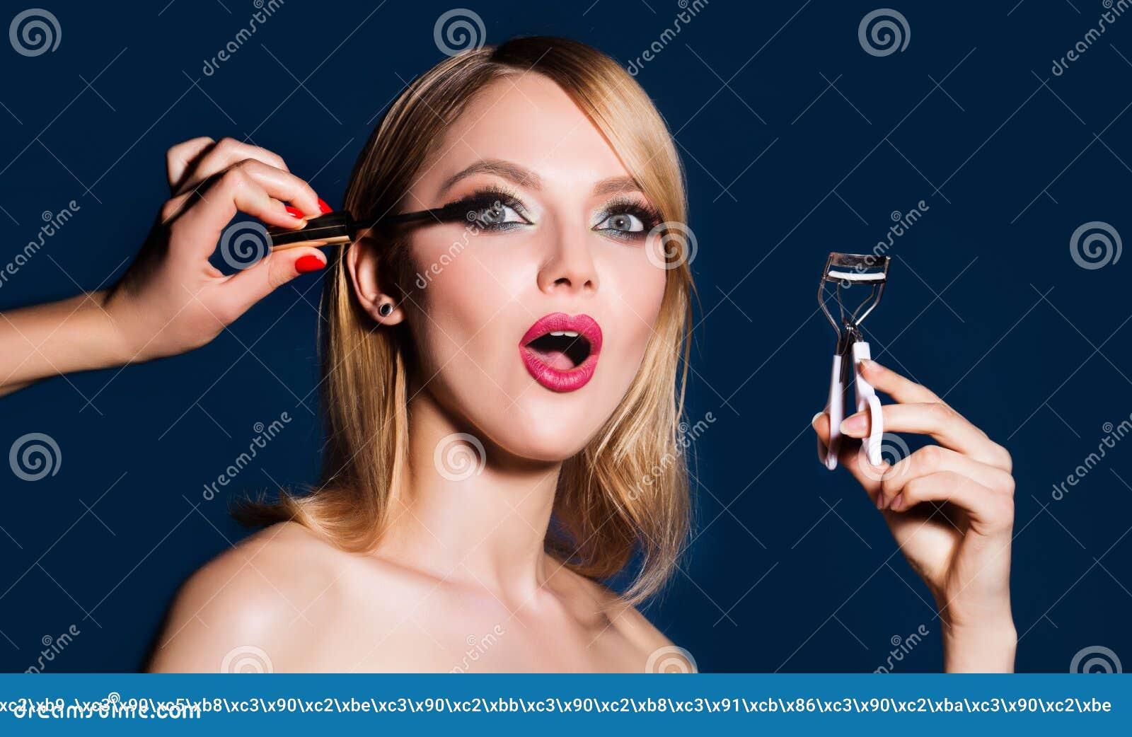 Il truccatore si applica la mascara ai cigli Trucco rosso luminoso delle labbra, pelle pulita perfetta, ombretti Donna che la fa