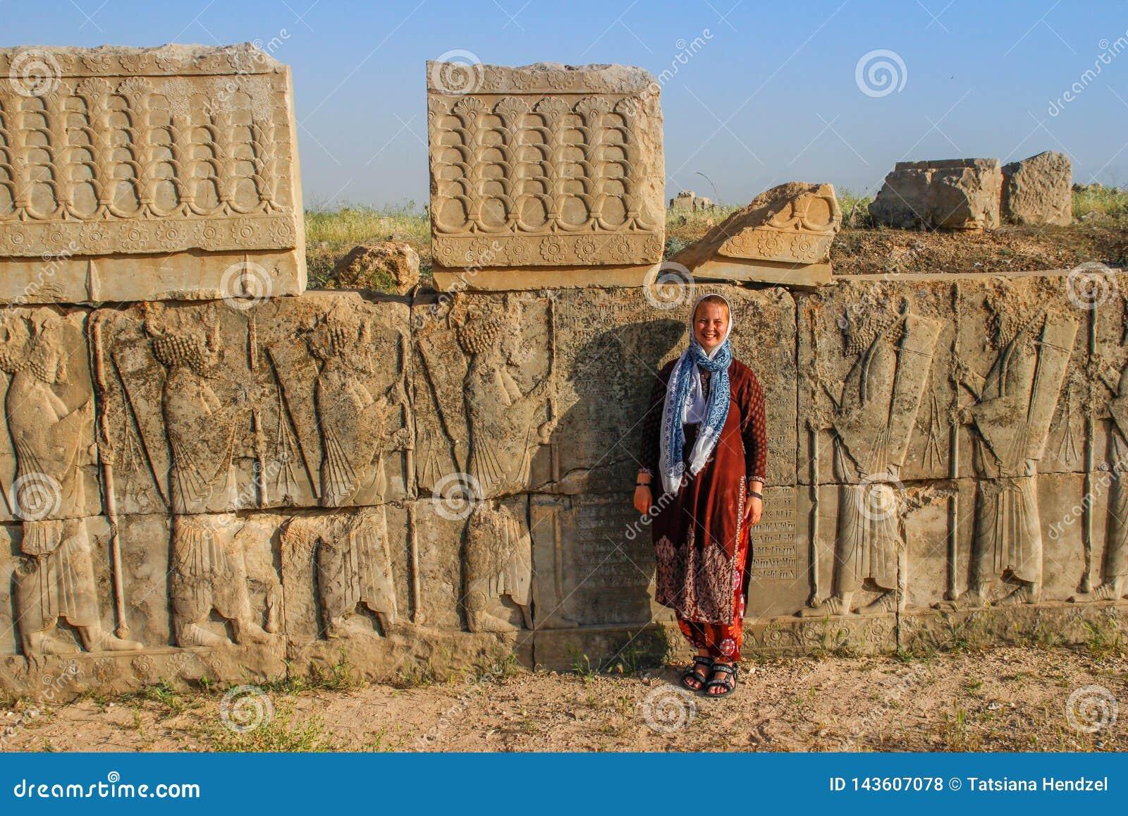 Il turista della giovane donna con una testa coperta sta sui precedenti dei bassorilievi famosi della capitale di Persia Iran - P