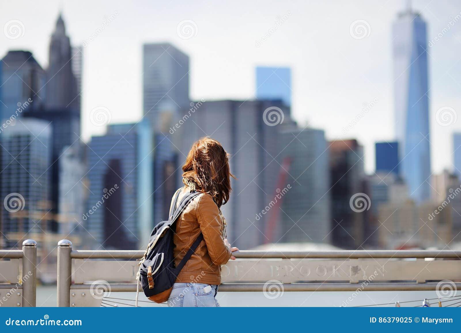 Il turista femminile gode della vista panoramica con i grattacieli di Manhattan a New York, U.S.A.