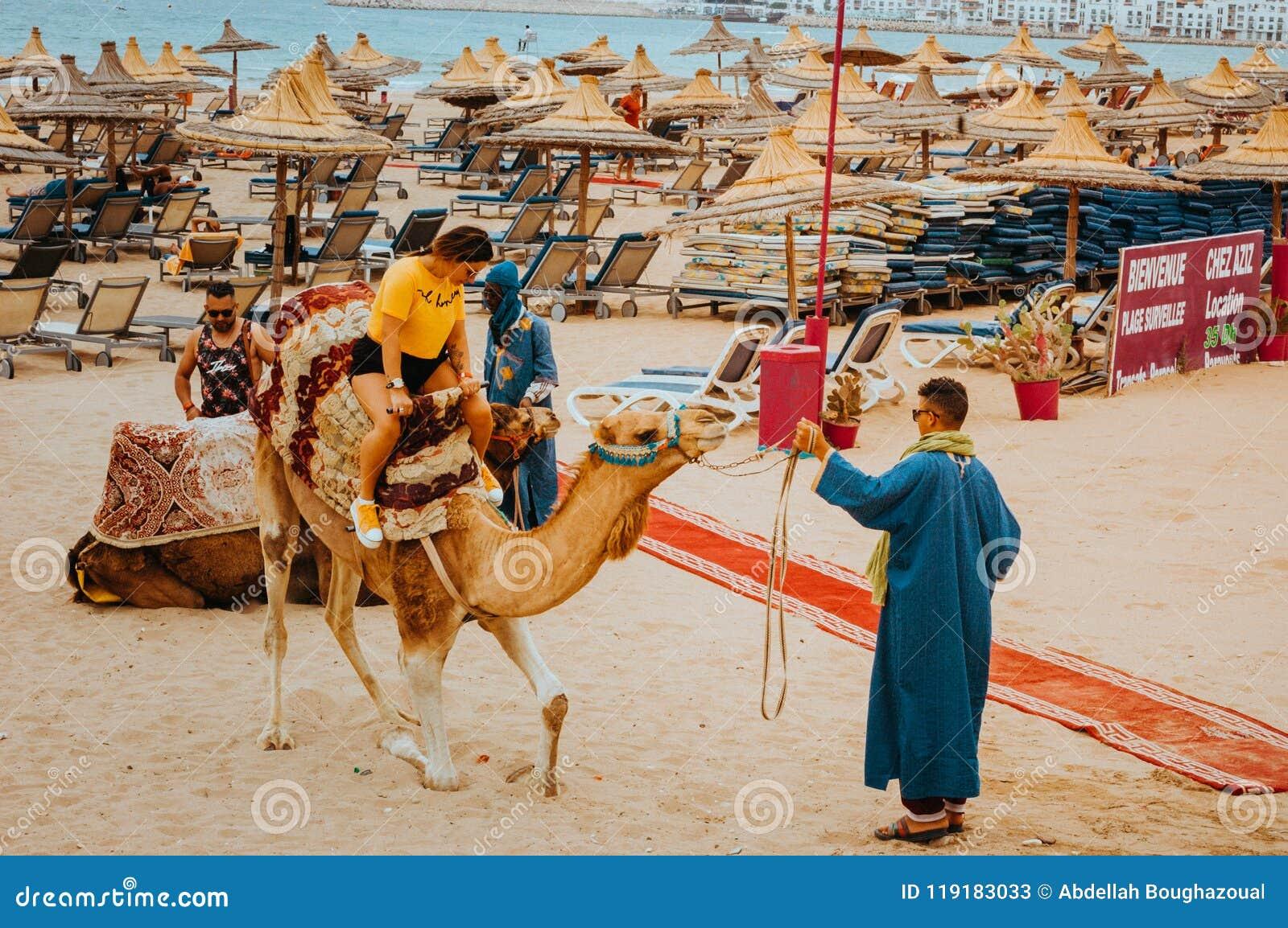 Il turista grazioso della giovane donna guida per la prima volta un cammello