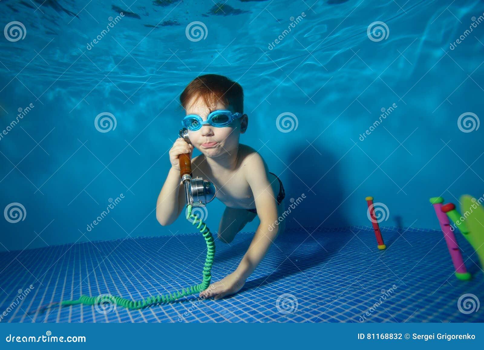 Il underwater del ragazzino nuota e gioca nello stagno con il microtelefono