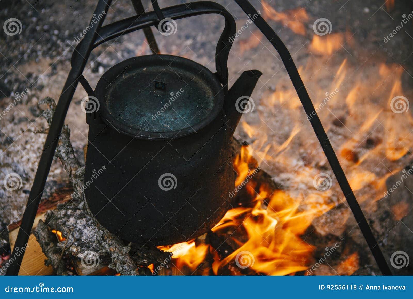 Il vecchio bollitore sta bruciando al palo, l acqua del punto di ebollizione dei turisti sul fuoco Fuoco di accampamento del fuoc