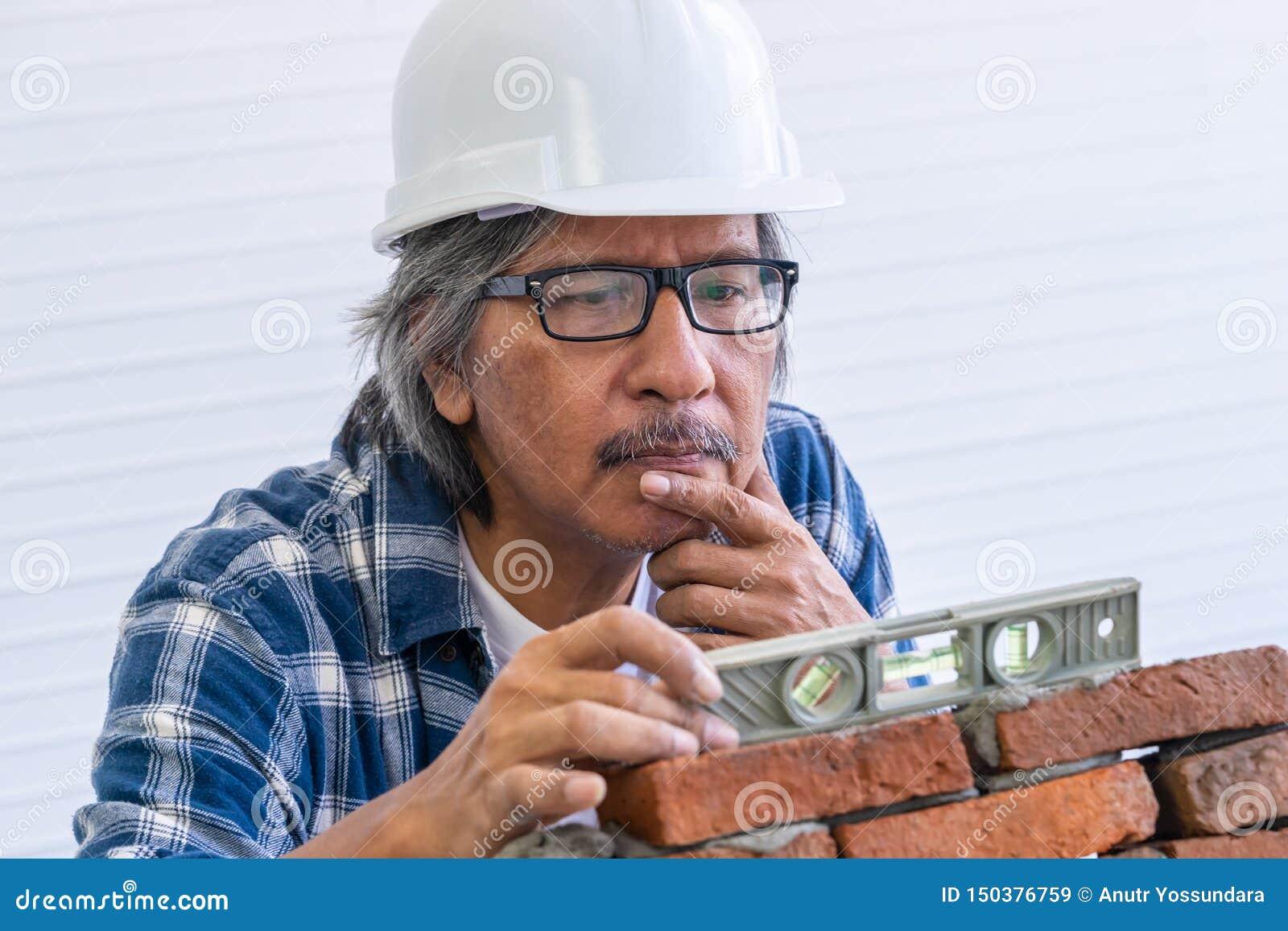 Il vecchio costruttore sta livellando il muro di mattoni