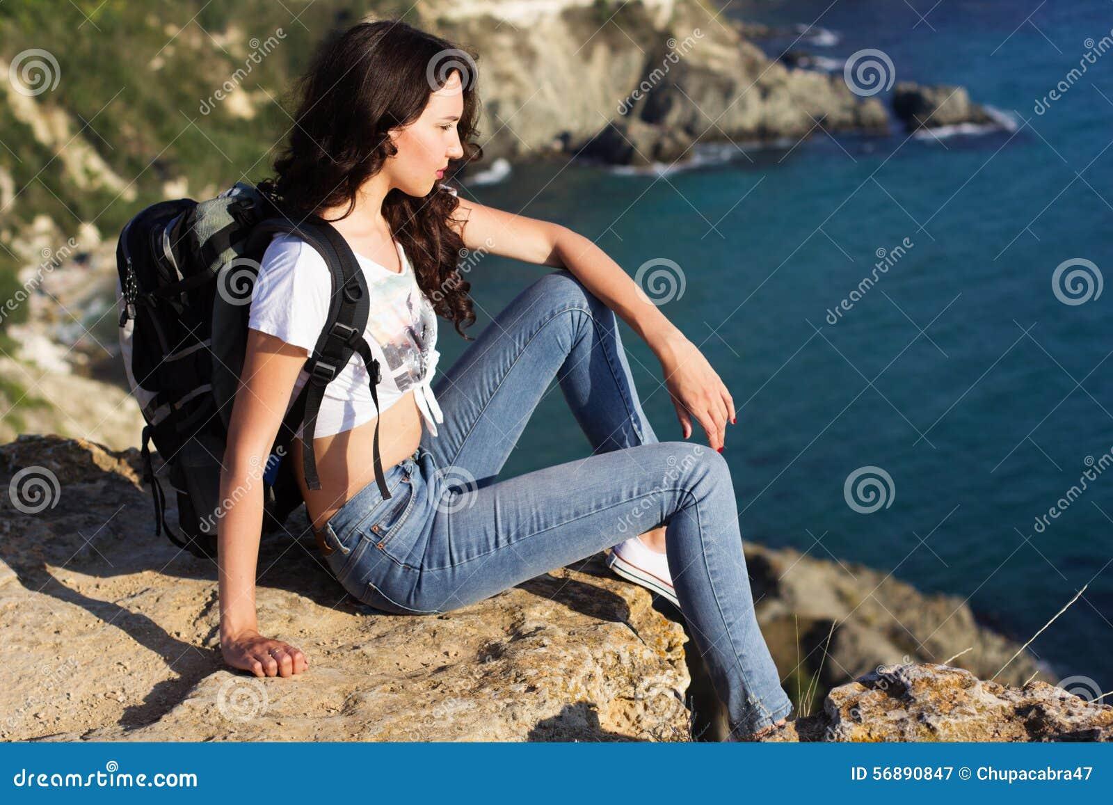 Il viaggiatore della ragazza sta sedendosi sulla roccia sopra la vista del mare