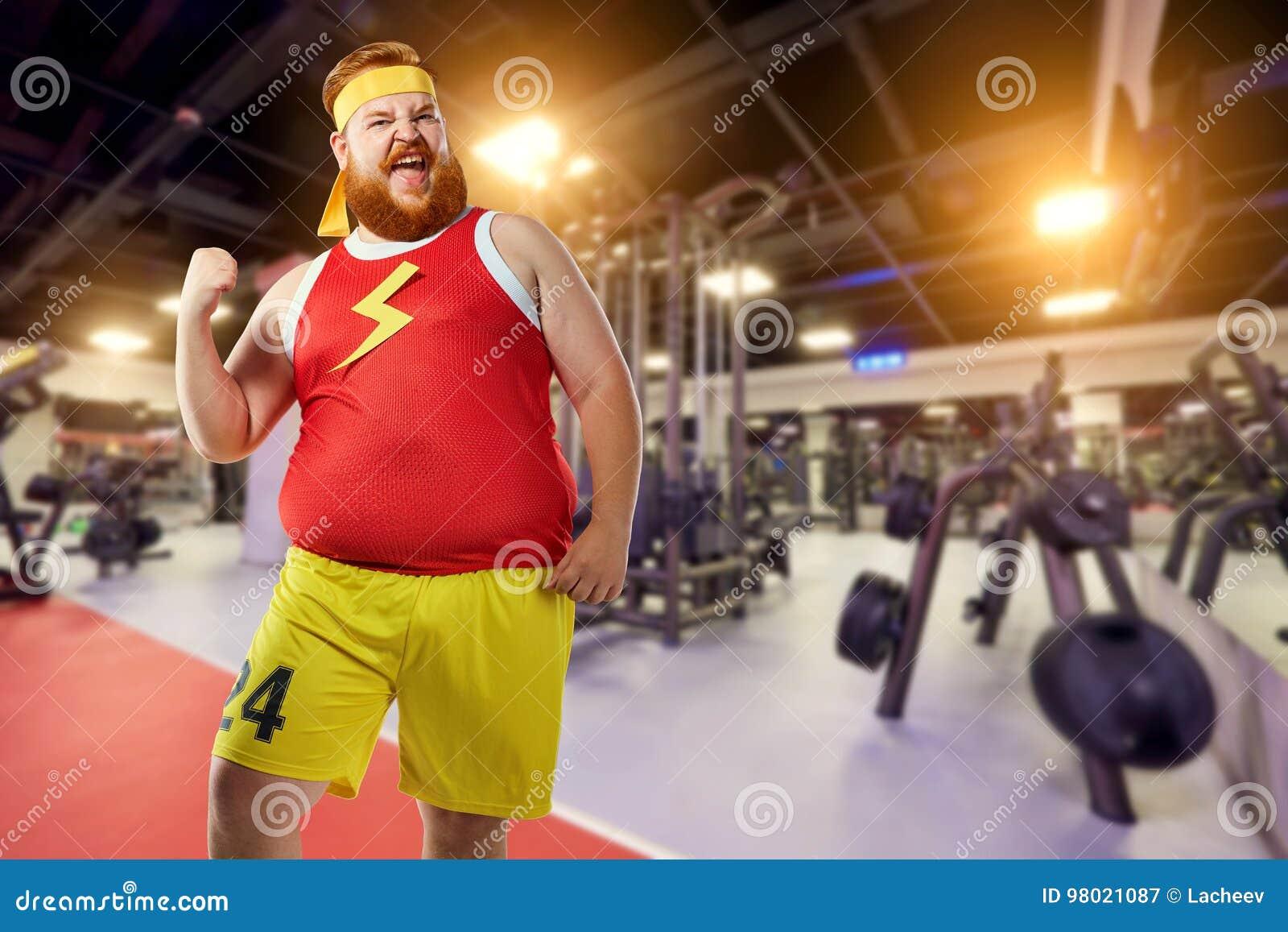 Il vincitore divertente grasso dell uomo sorride in vestiti di sport nella palestra