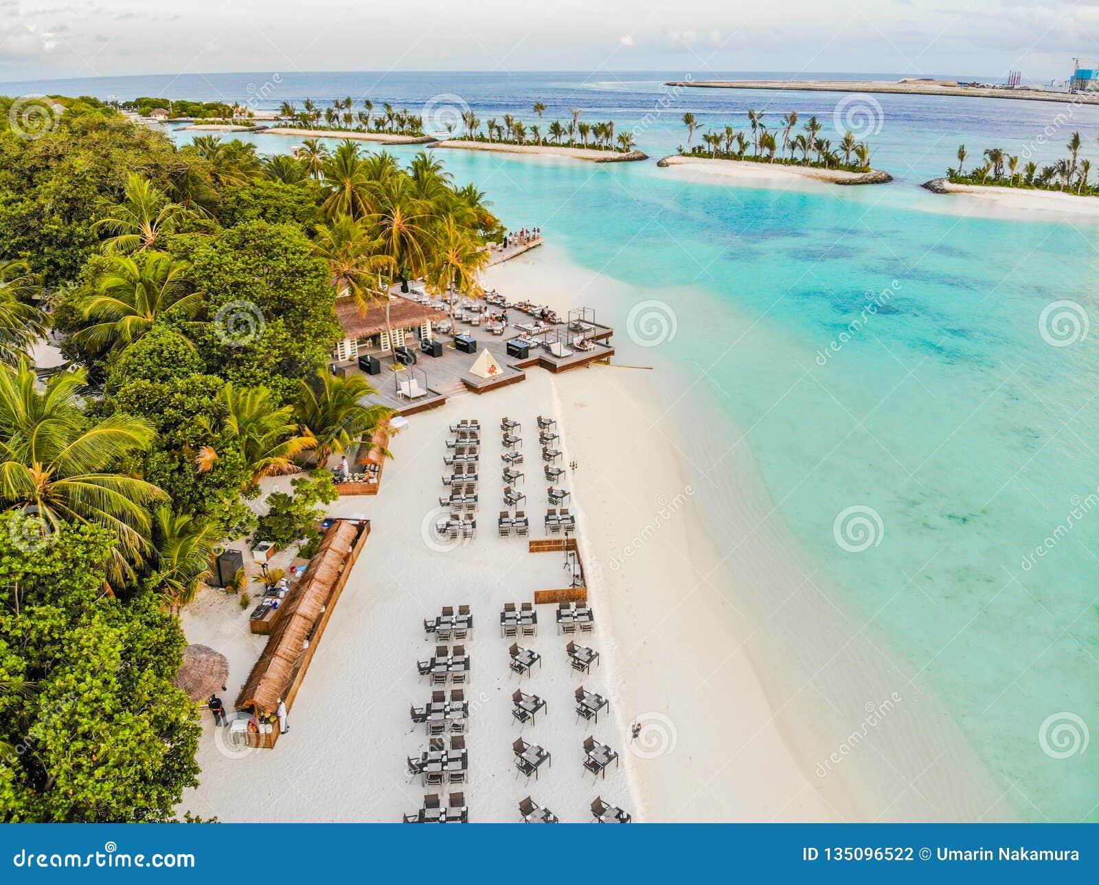 Ilha de surpresa em Maldivas, nas águas bonitas de turquesa e no Sandy Beach branco com fundo do céu azul
