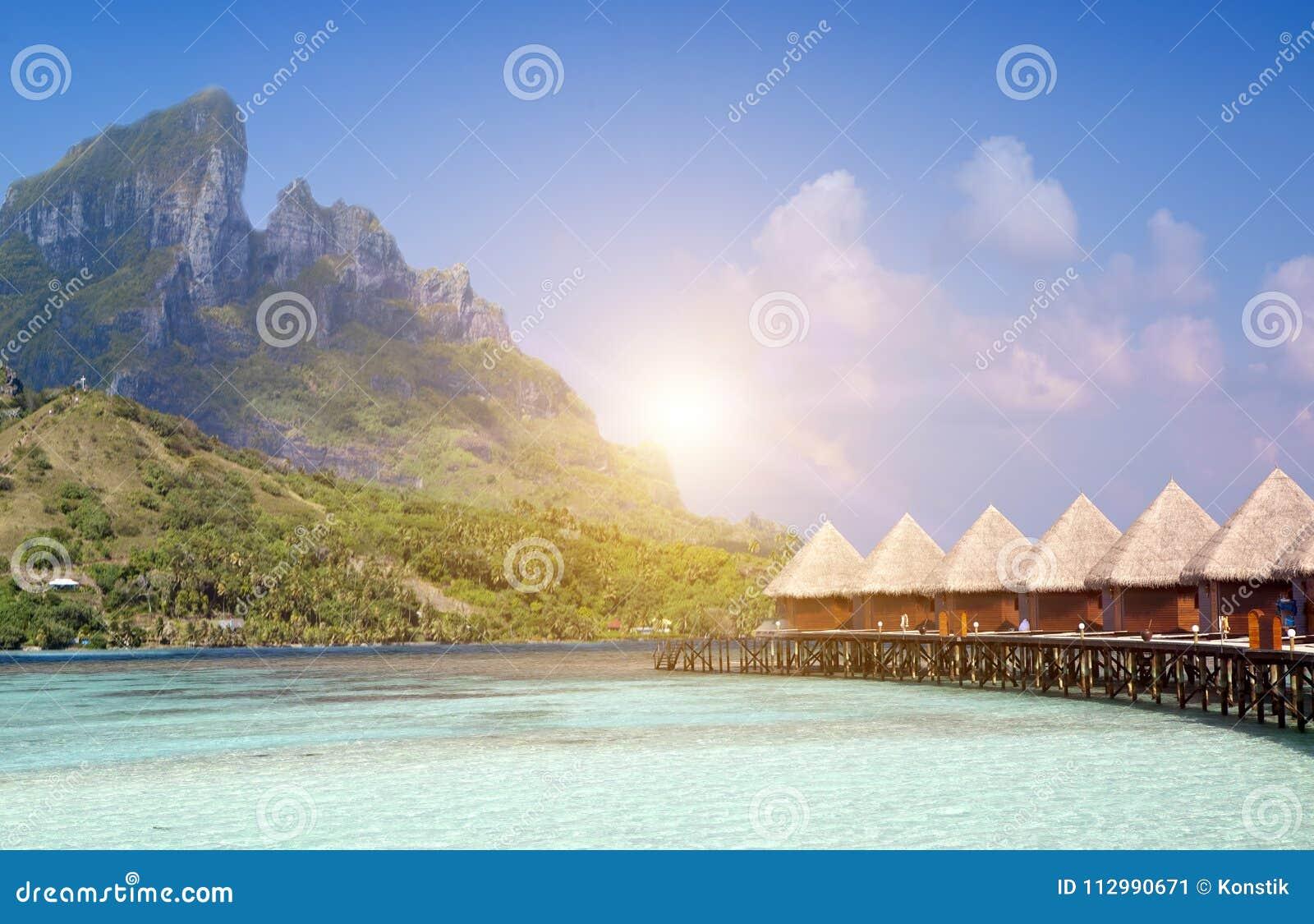 Ilha tropical bonita de Maldivas, casas de campo da água, bungalow no mar e a montanha em um fundo