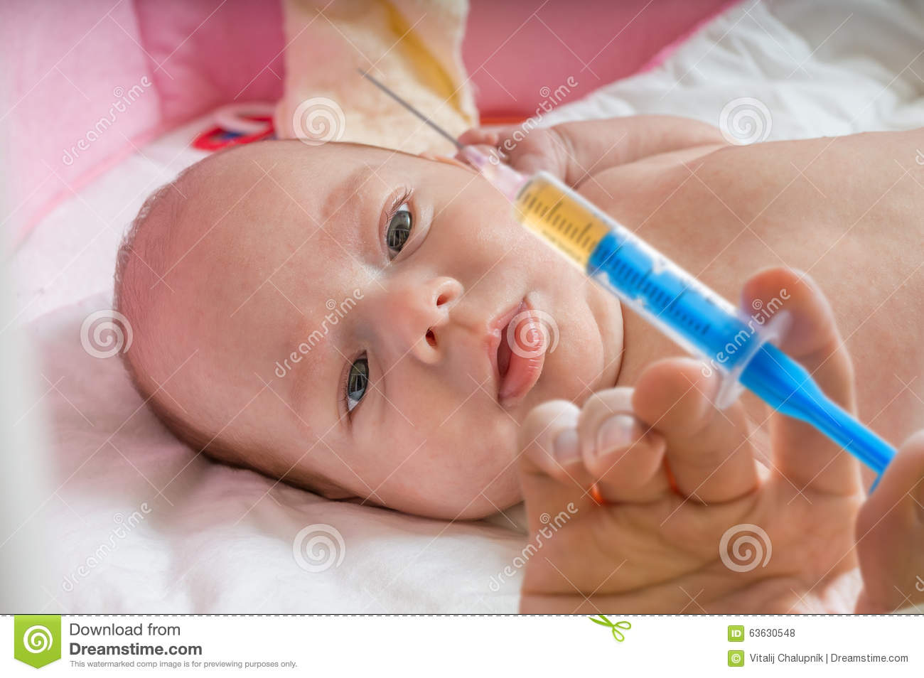 Ill baby is starring on syringe with immunization vaccine