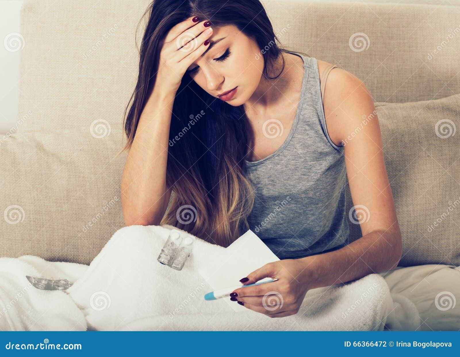 Ill del naso di salto della giovane donna a letto con la temperatura