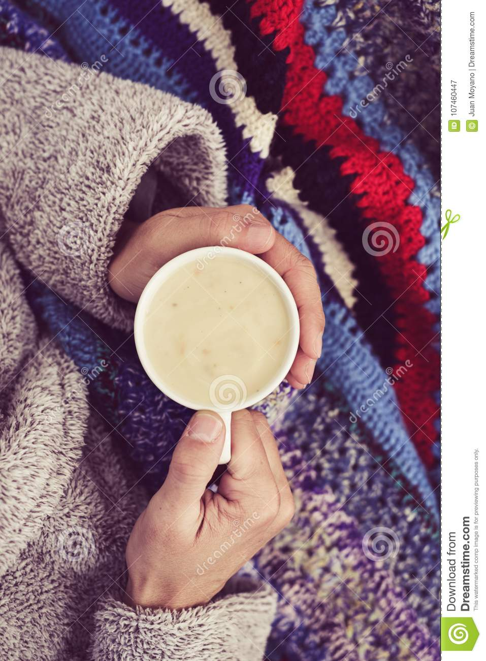 Ill man warming up with a cup of soup